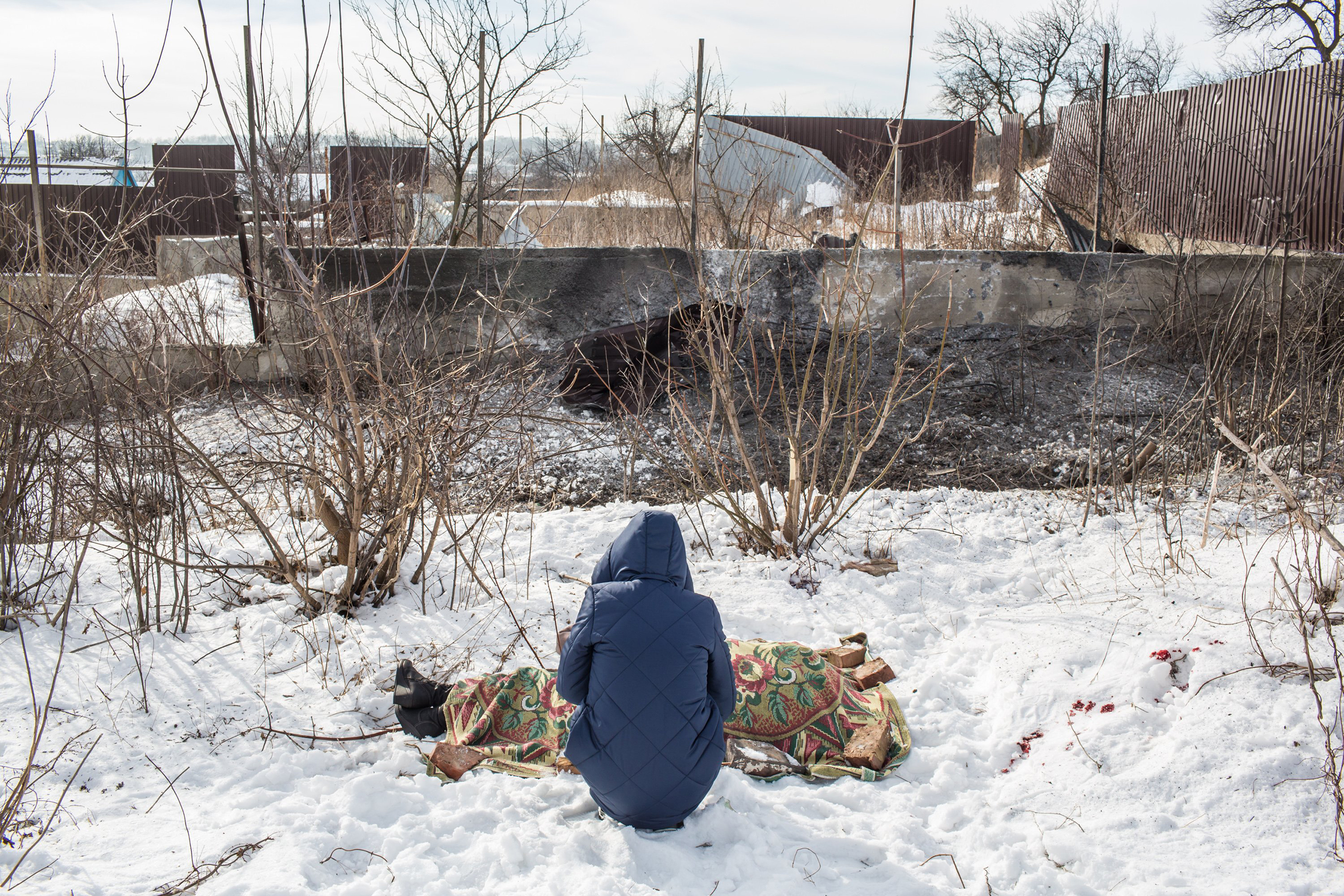 Nadiya Volkova, 24, grieves over the body of her mother Katya Volkova, 60, who was killed by shelling in Avdiivka, Ukraine, as she walked to a store early on Feb. 1, 2017.