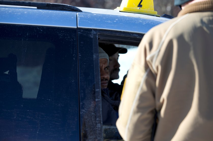 A man who claimed to be from Sudan looks out the taxi window as a U.S. border patrol officer checks his passport and visa at the U.S.-Canada border into Hemmingford, Canada, from Champlain in New York, U.S., February 17, 2017. REUTERS/Christinne Muschi - RTSZ6PE