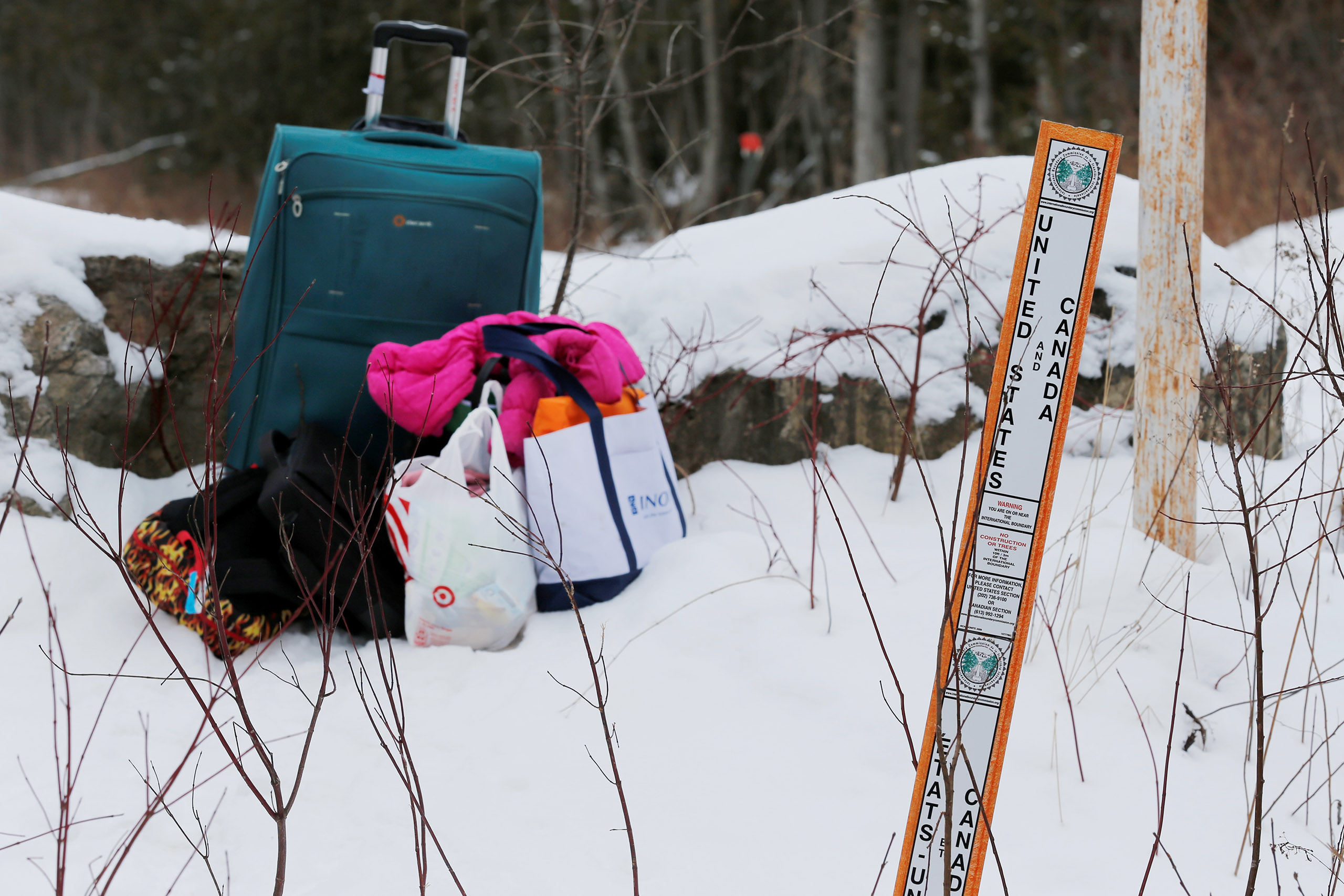 Luggage sits on the United States side of the border after a woman who told police that she and her family were from Sudan is taken into custody by Royal Canadian Mounted Police (RCMP) officers after arriving by taxi and walking across the U.S.-Canada border into Hemmingford, Quebec, on Feb. 12, 2017.