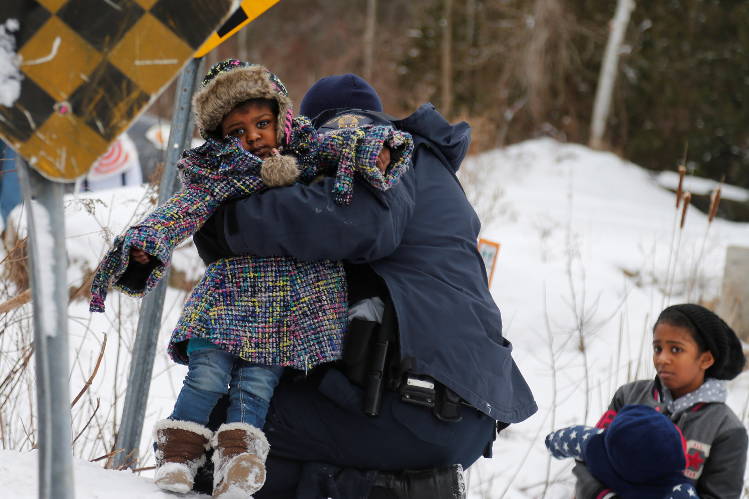 A child is helped up a hill by Royal Canadian Mounted Police (RCMP) officers after a family arriving by taxi and claiming to be from Sudan are taken into custody after walking across the U.S.-Canada border into Hemmingford, Quebec, on Feb. 12, 2017.