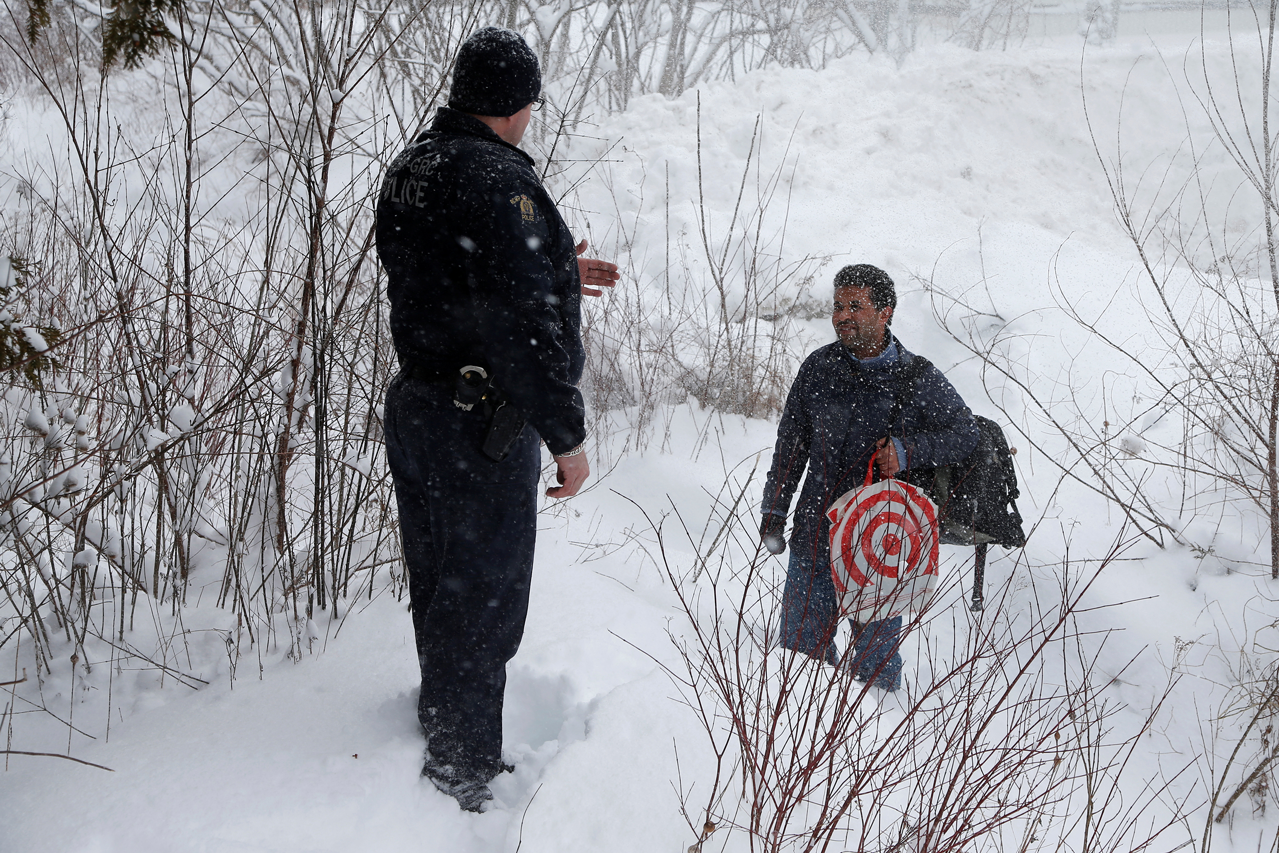 A man who told police he was from Sudan is confronted by a Royal Canadian Mounted Police (RCMP) officer as he attempts to cross the U.S.-Canada border into Hemmingford, Quebec, on Feb. 13, 2017.