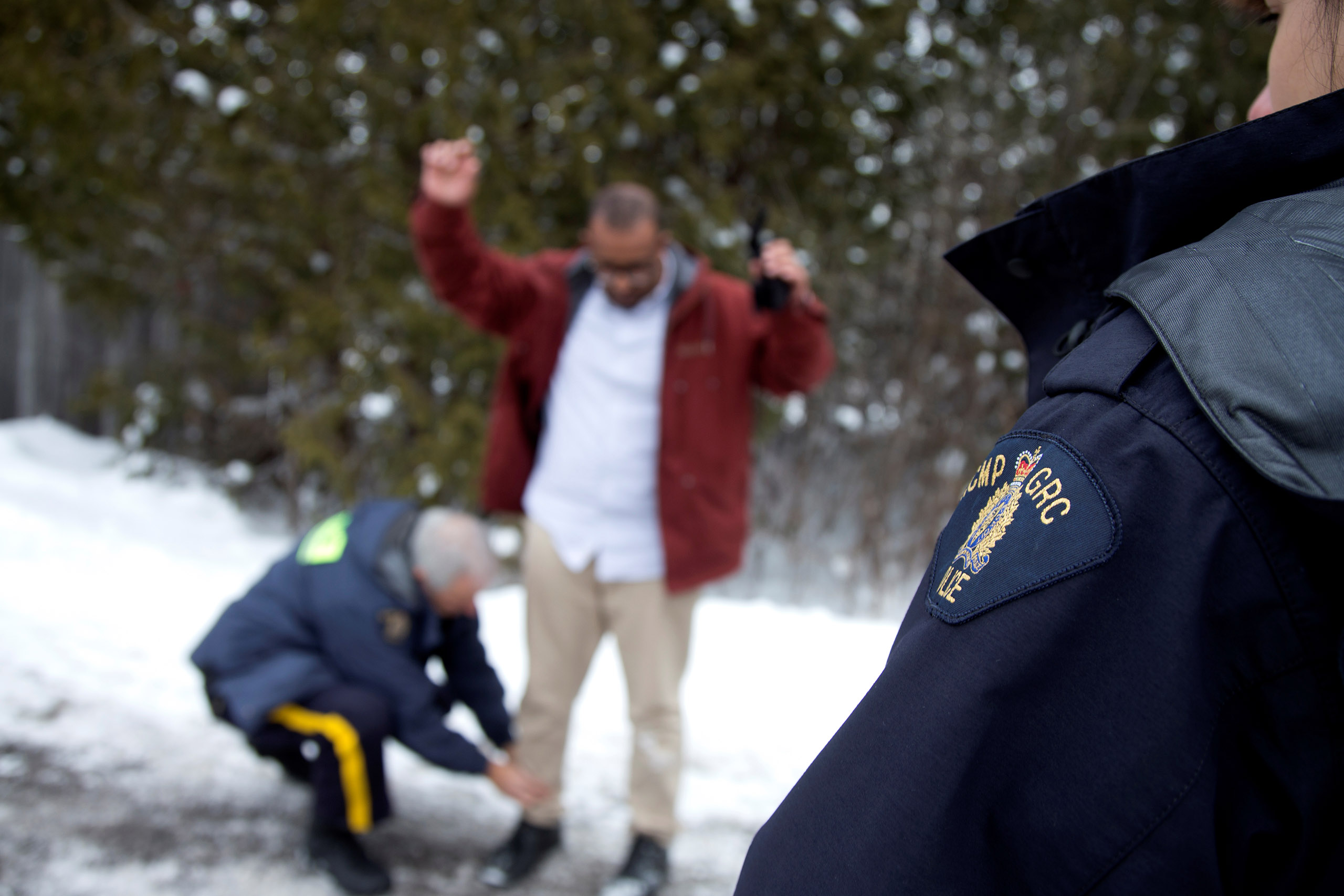 A man from Yemen is taken into custody by Royal Canadian Mounted Police (RCMP) officers after walking across the U.S.-Canada border into Hemmingford, Quebec, on Feb. 14, 2017.