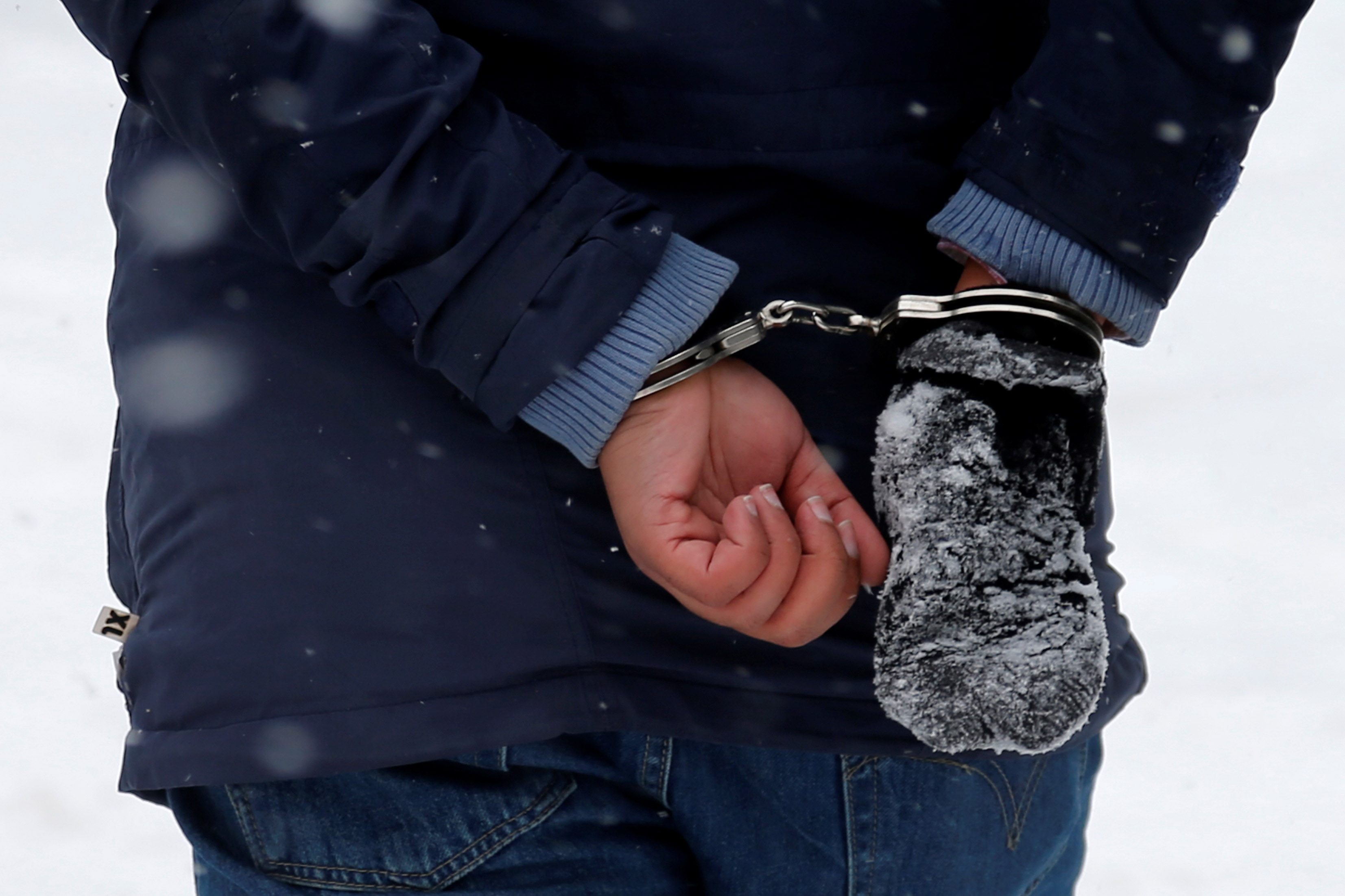 A man who told police that he was from Sudan is taken into custody by Royal Canadian Mounted Police (RCMP) officers after arriving by taxi and walking across the U.S.-Canada border into Hemmingford, Quebec, on Feb. 13, 2017.