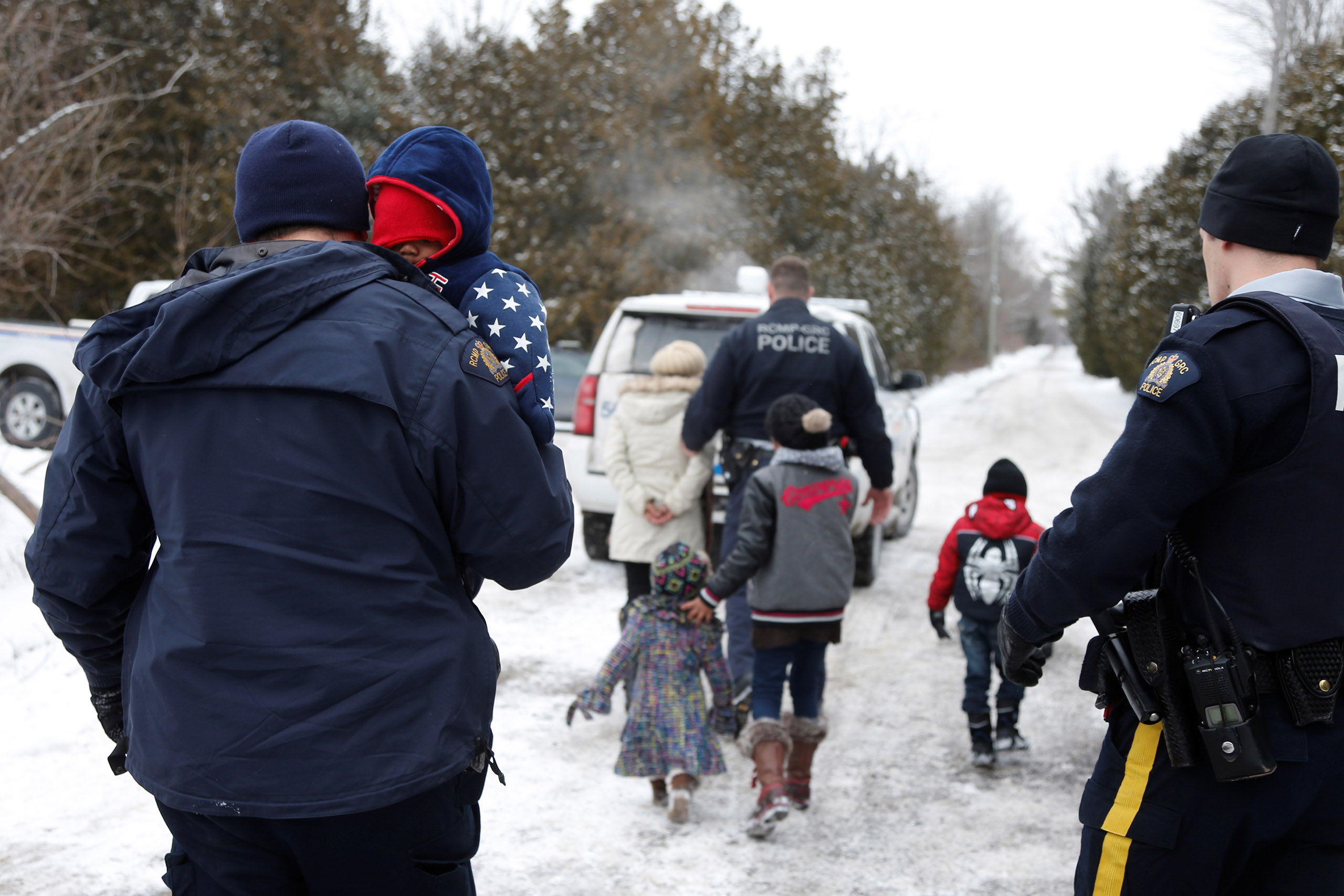 A woman who told police that she and her family were from Sudan is taken into custody by Royal Canadian Mounted Police (RCMP) officers after arriving by taxi and walking across the U.S.-Canada border into Hemmingford, Quebec, on Feb. 12, 2017.