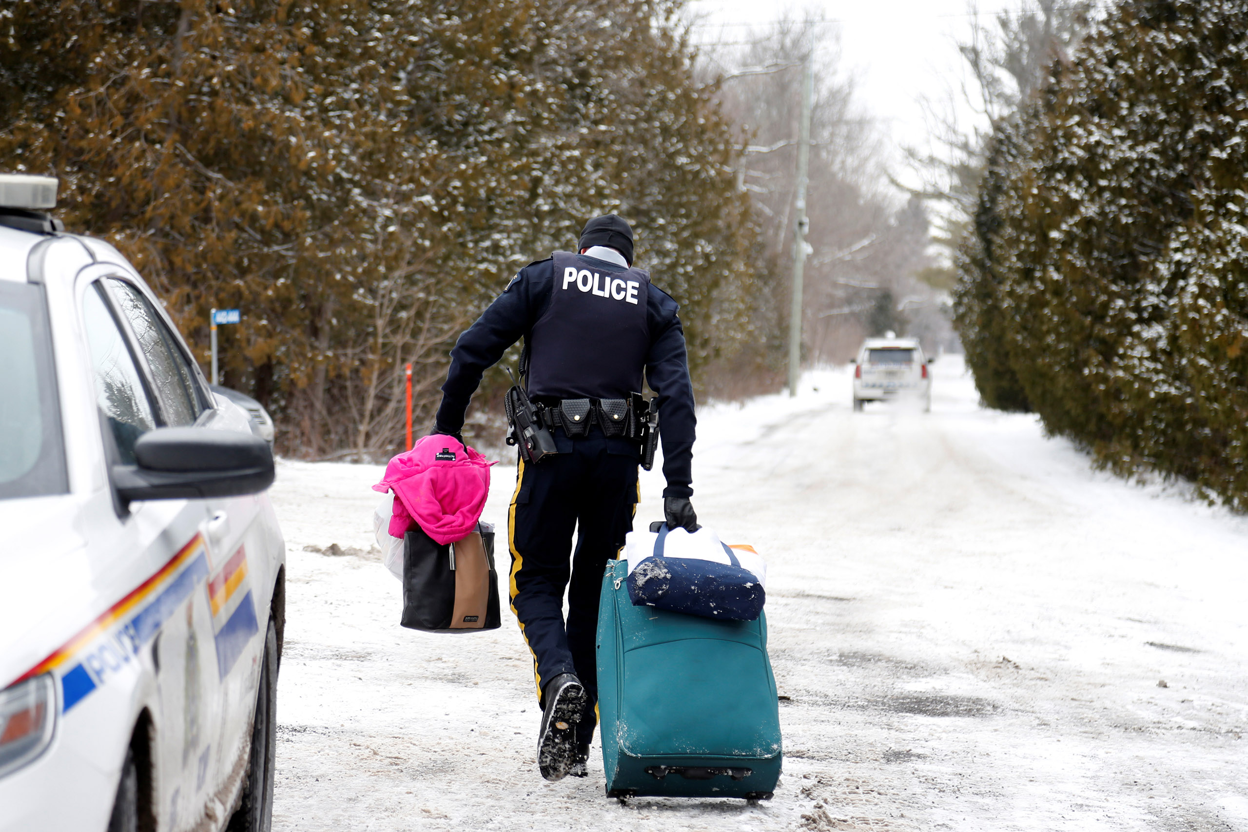 A Royal Canadian Mounted Police (RCMP) officer carries luggage of a woman and her family who told police they were from Sudan and were taken into custody after arriving by taxi and walking across the U.S.-Canada border into Hemmingford, Quebec, on Feb. 12, 2017.