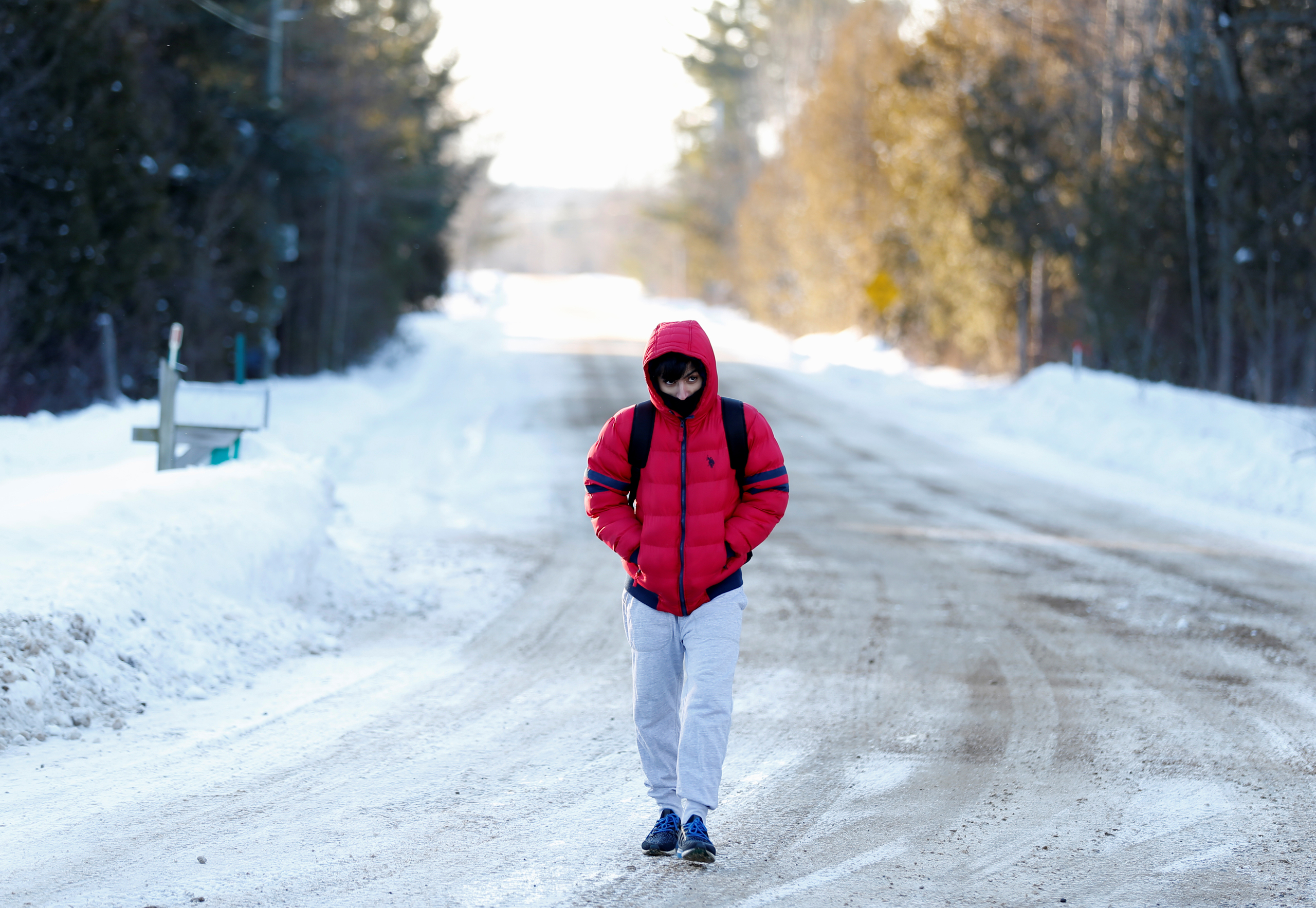 A man who said his name was Abdullah and that he was a student from Yemen walks towards the U.S.-Canada border to cross into Hemmingford, Canada, from Champlain, N.Y., on Feb.17, 2017.