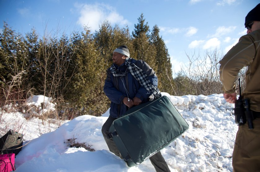 A man who claimed to be from Sudan throws his family's suitcases towards the border as he is detained by a U.S. border patrol officer after his family crossed the U.S.-Canada border into Hemmingford, Canada, from Champlain in New York, U.S., February 17, 2017. REUTERS/Christinne Muschi - RTSZ6NV
