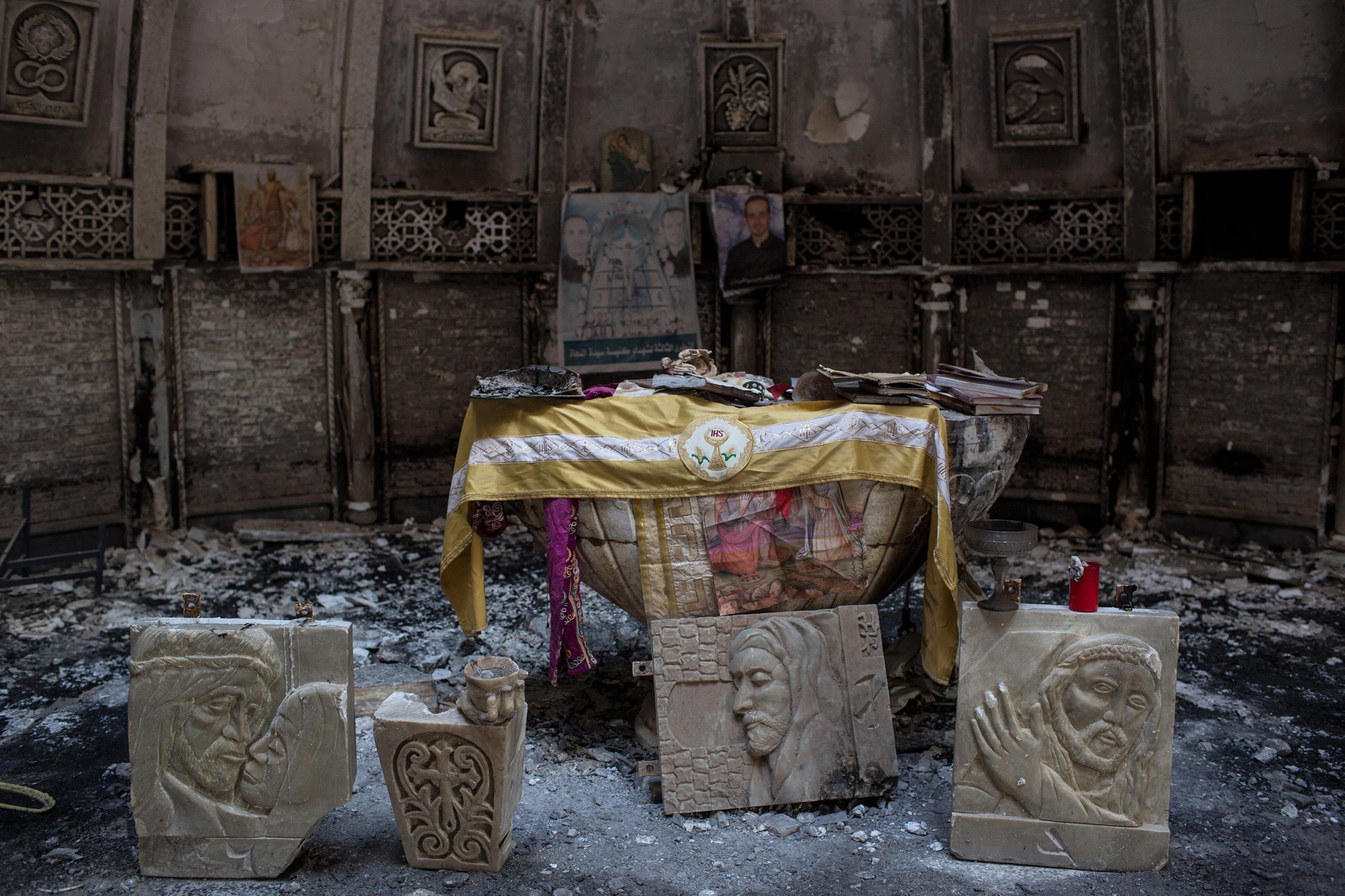 Salvaged books and other items are placed around the altar of a church, burned and destroyed by ISIS during the group's occupation of the predominantly Christian town of Qaraqosh, Iraq, on Dec. 27, 2016.