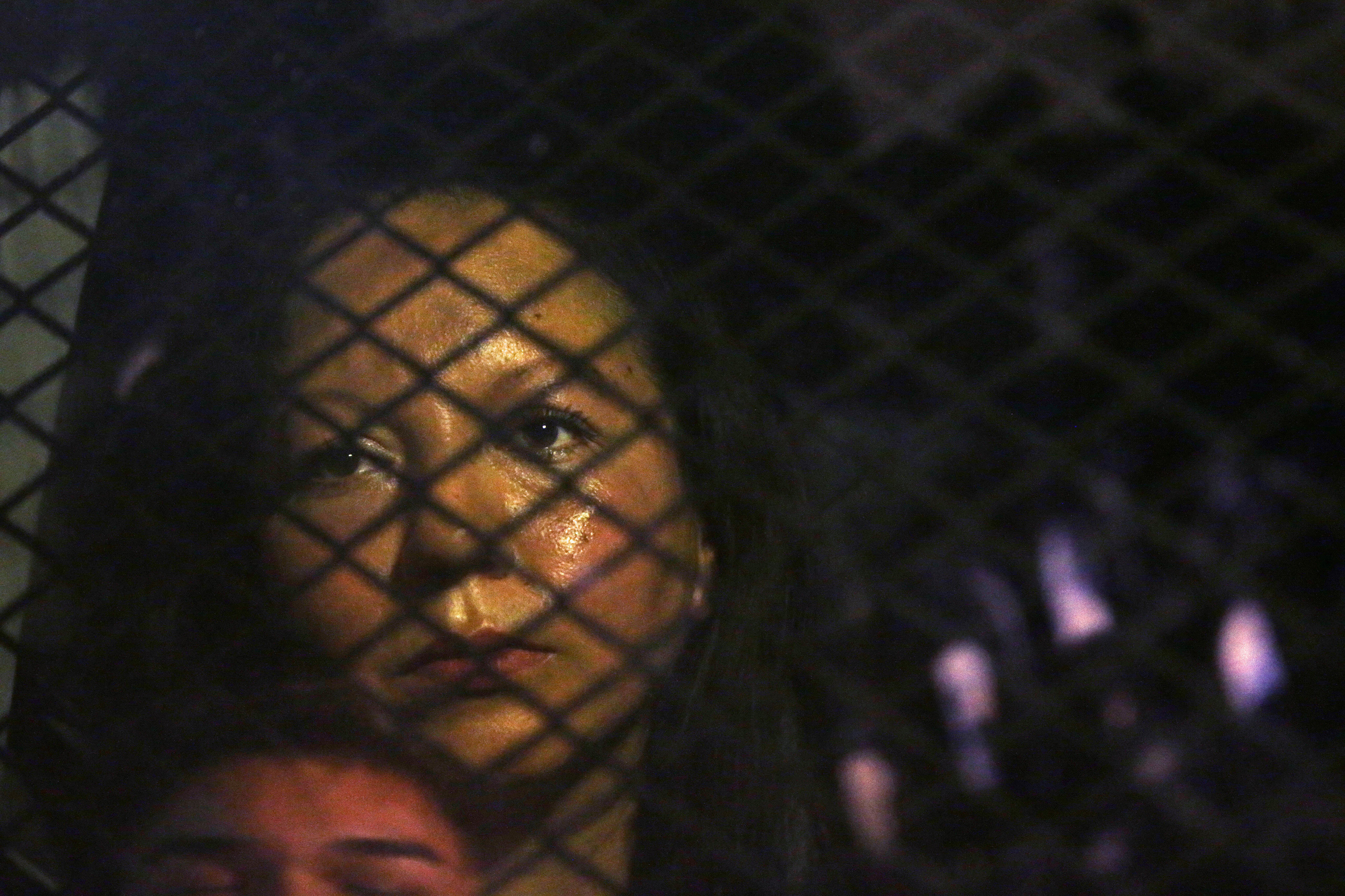 Guadalupe Garcia de Rayos is locked in a van that is stopped in the street by protesters outside the Immigration and Customs Enforcement facility in Phoenix on Feb. 8, 2017. Apparently fearing her deportation, activists blocked the gates surrounding the office near central Phoenix in what the Arizona Republic says was an effort to block several vans and a bus inside from leaving.