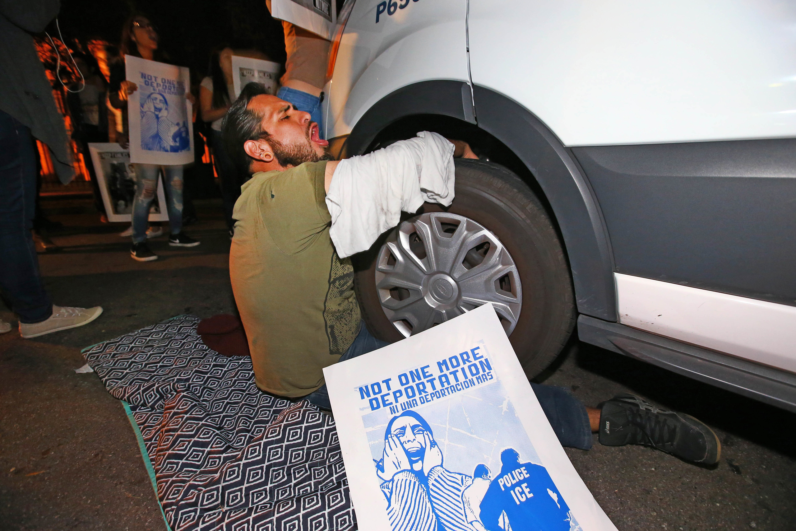 A protester locked himself to the van carrying Guadalupe Garcia de Rayos that is stopped by protesters outside the Immigration and Customs Enforcement facility, in Phoenix on Feb. 8, 2017.