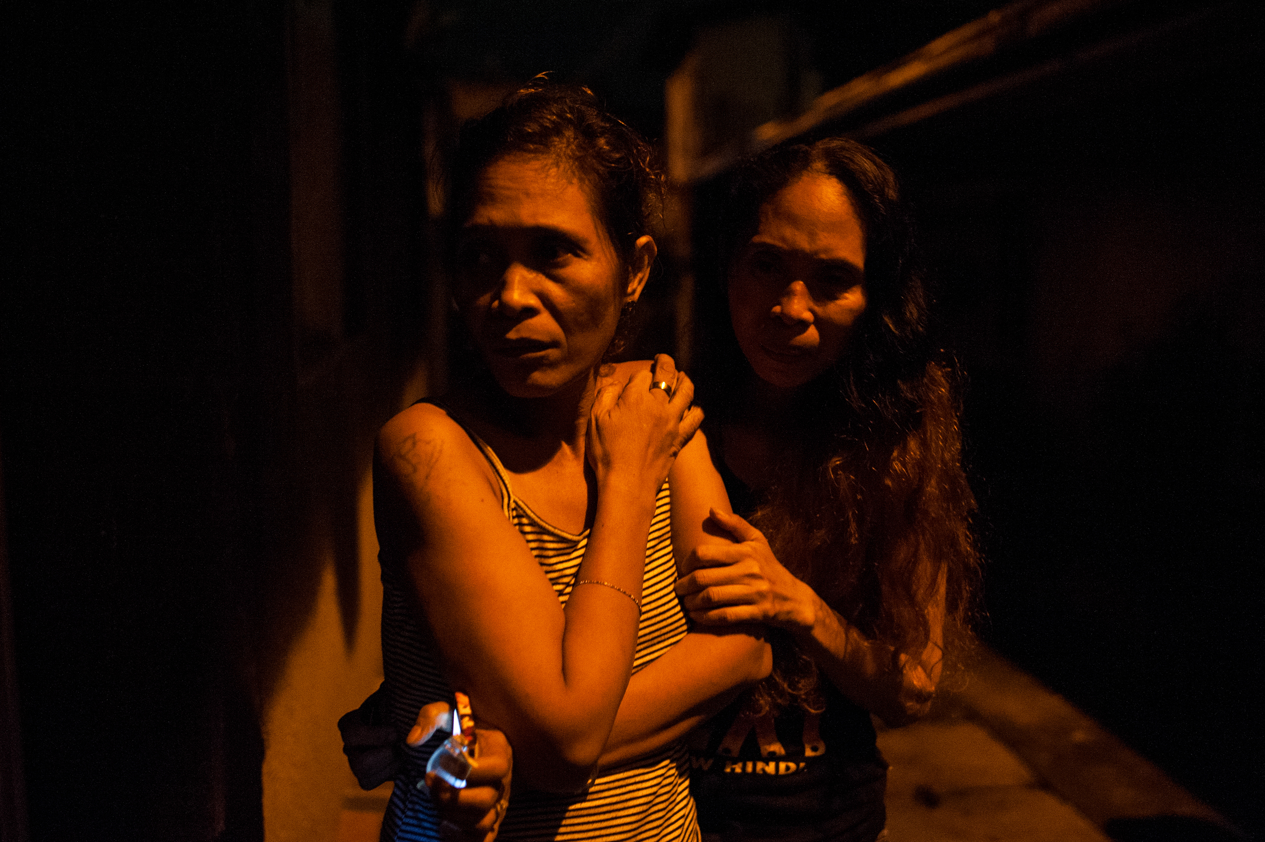 Two women watch as the body of their kin is examined by police after masked assailants barged into their home and dragged him into the streets and shot him in Manila in September 2016.