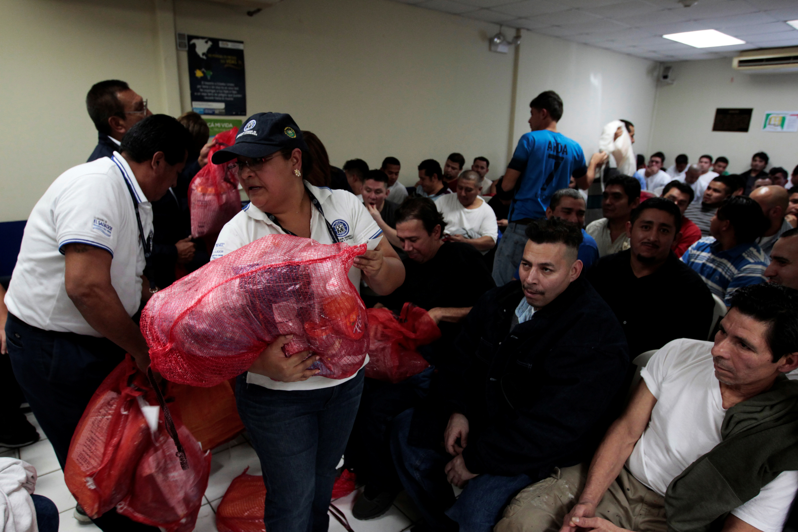 Immigration workers process bags with belongings at an immigration facility after a flight carrying illegal immigrants from the U.S. arrived at the Oscar Arnulfo Romero International Airport in San Luis Talpa, El Salvador, on Jan. 27, 2017.