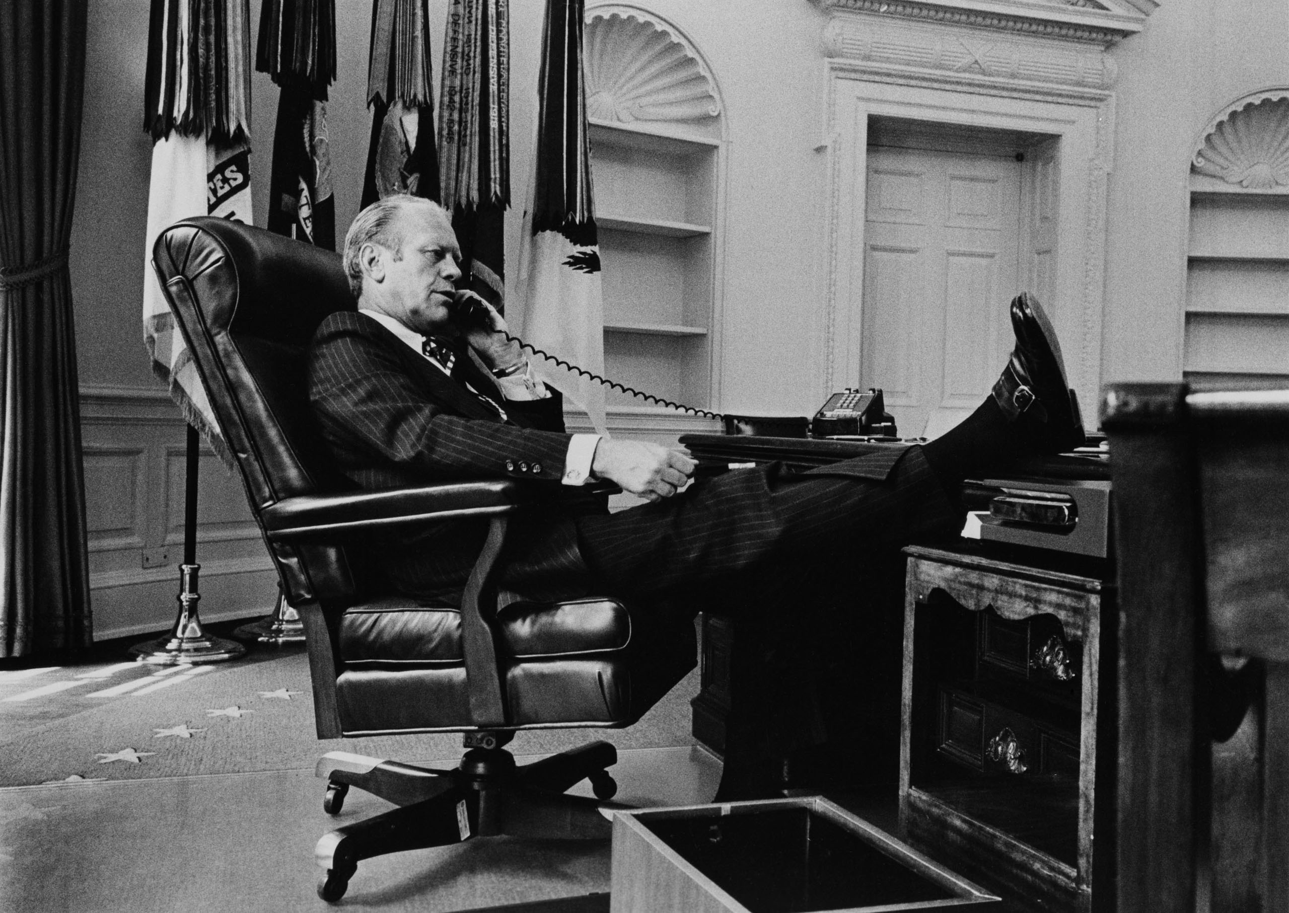 U.S. President Gerald R. Ford takes a call at his desk in the Oval Office on August 11, 1974 in Washington, D.C. The bookshelves are empty due to ex-President Richard M. Nixon's staff packing up two days prior. Ford stepped into office as president on August 9th after the resignation of Nixon.