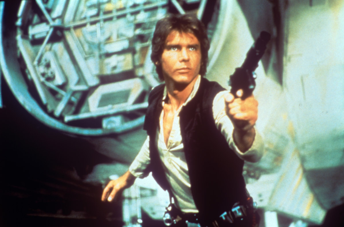 In a scene from George Lucas' epic space opera Star Wars, the American actor Harrison Ford as rebel smuggler Han Solo draws a gun against enemies; behind him can be seen a fantastic space shuttle. USA, 1977.