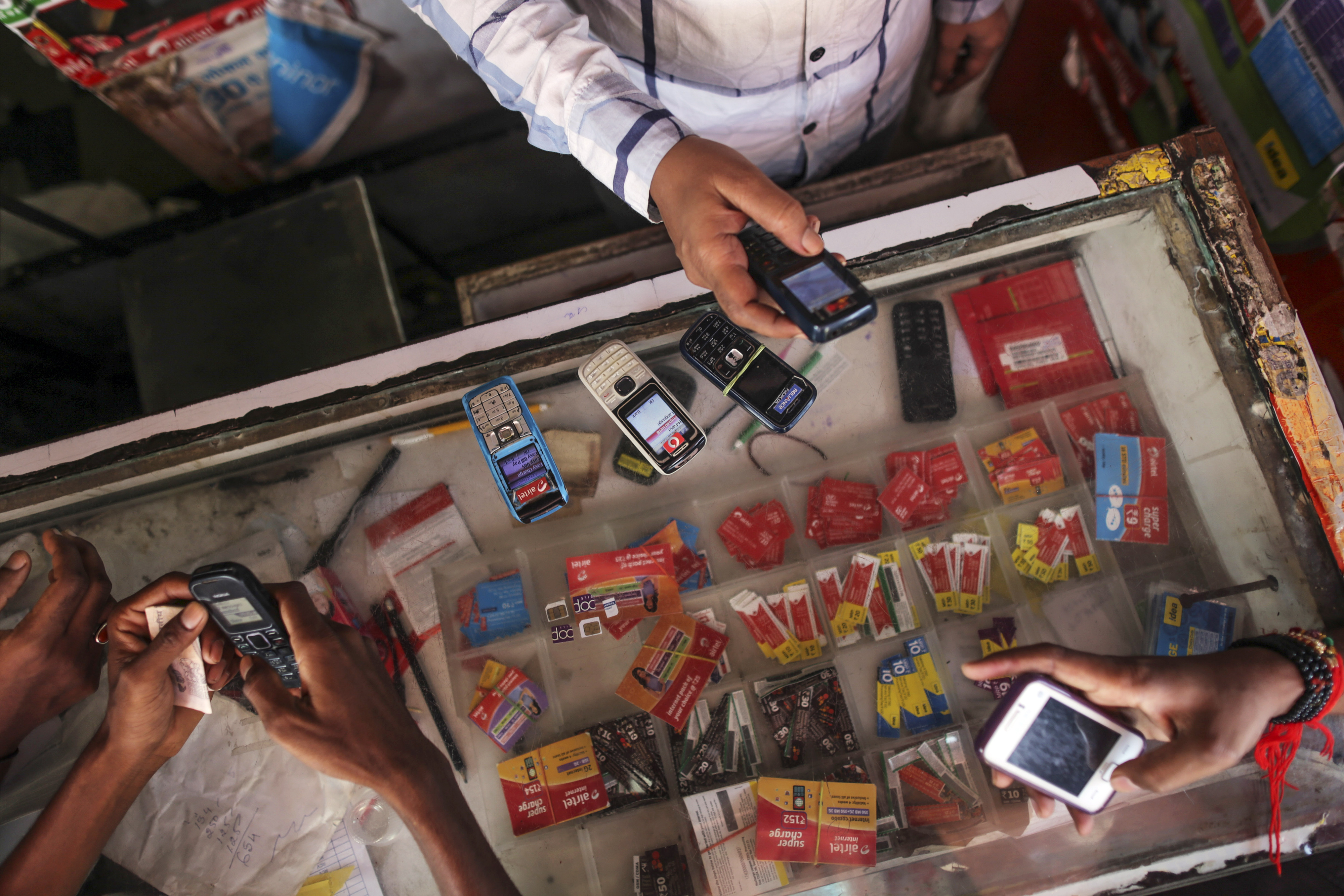 Customers wait to recharge their mobile phones at a mobile-phone store in Mumbai on Aug. 12, 2014