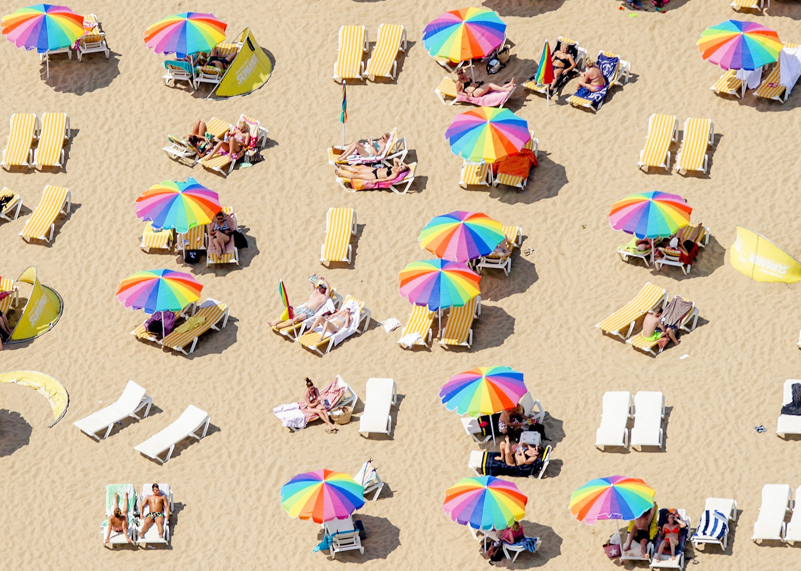 An aerial view shows sunbathers sitting under colorful umbrellas on the beach in Scheveningen, the Netherlands, on July 1, 2015, on a warm summer day.