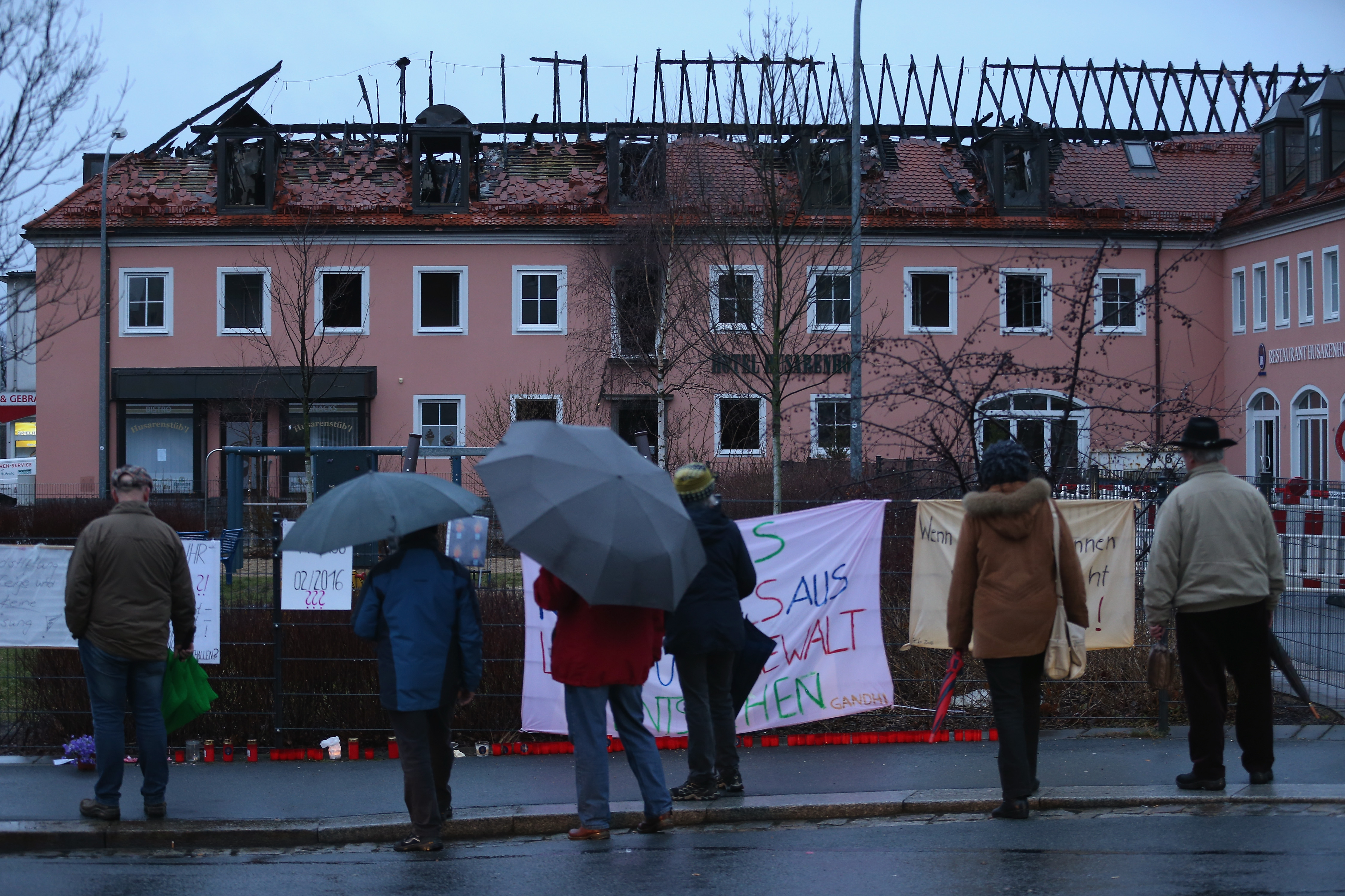 Bystanders look at the burnt-out remains of a former hotel that was to serve as a shelter for 300 asylum applicants following a fire in the early morning on February 21, 2016 in Bautzen, Germany.