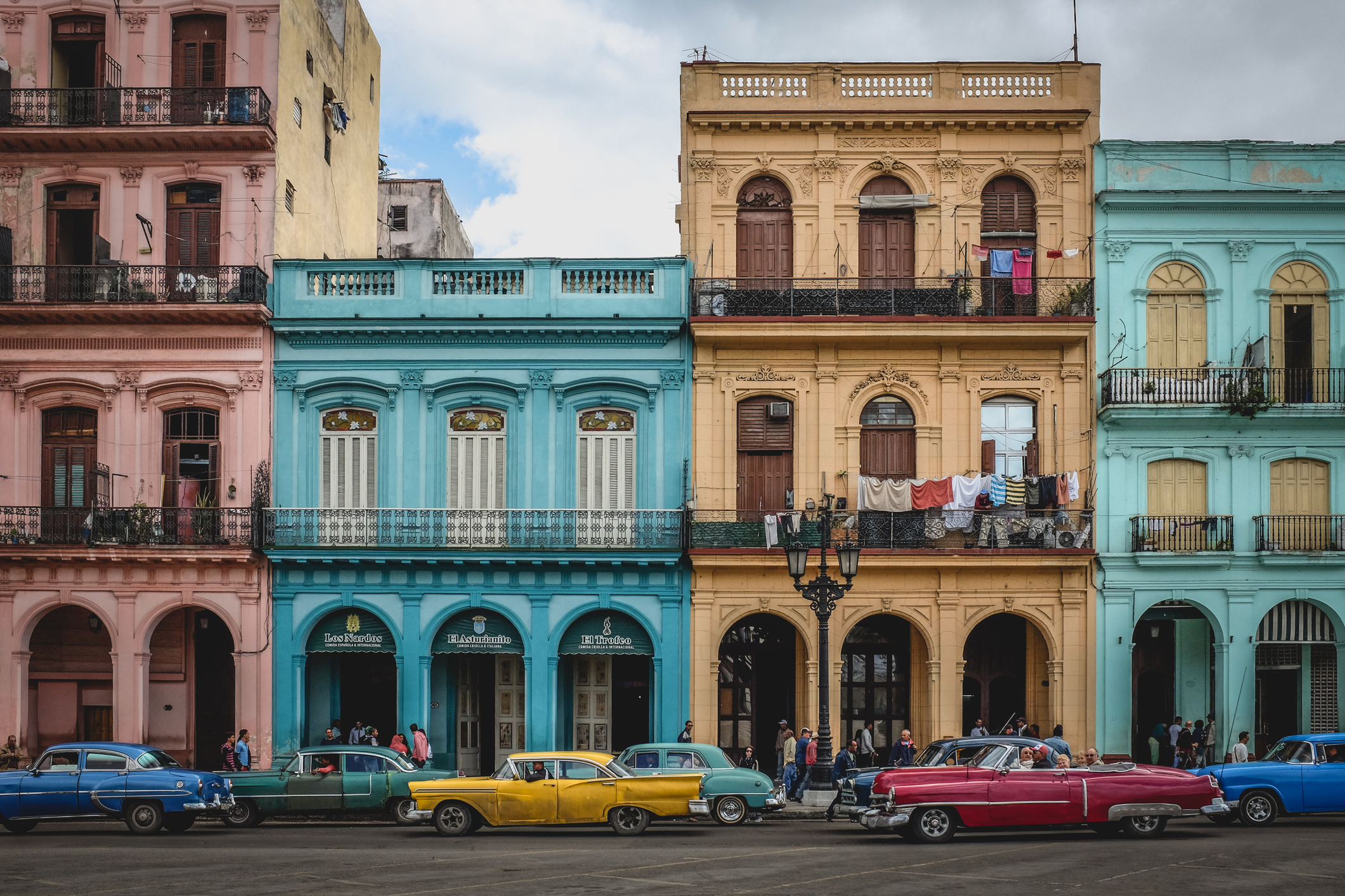 A photo of colonial buildings in old Havana, with many colorful old american cars driving along the road.