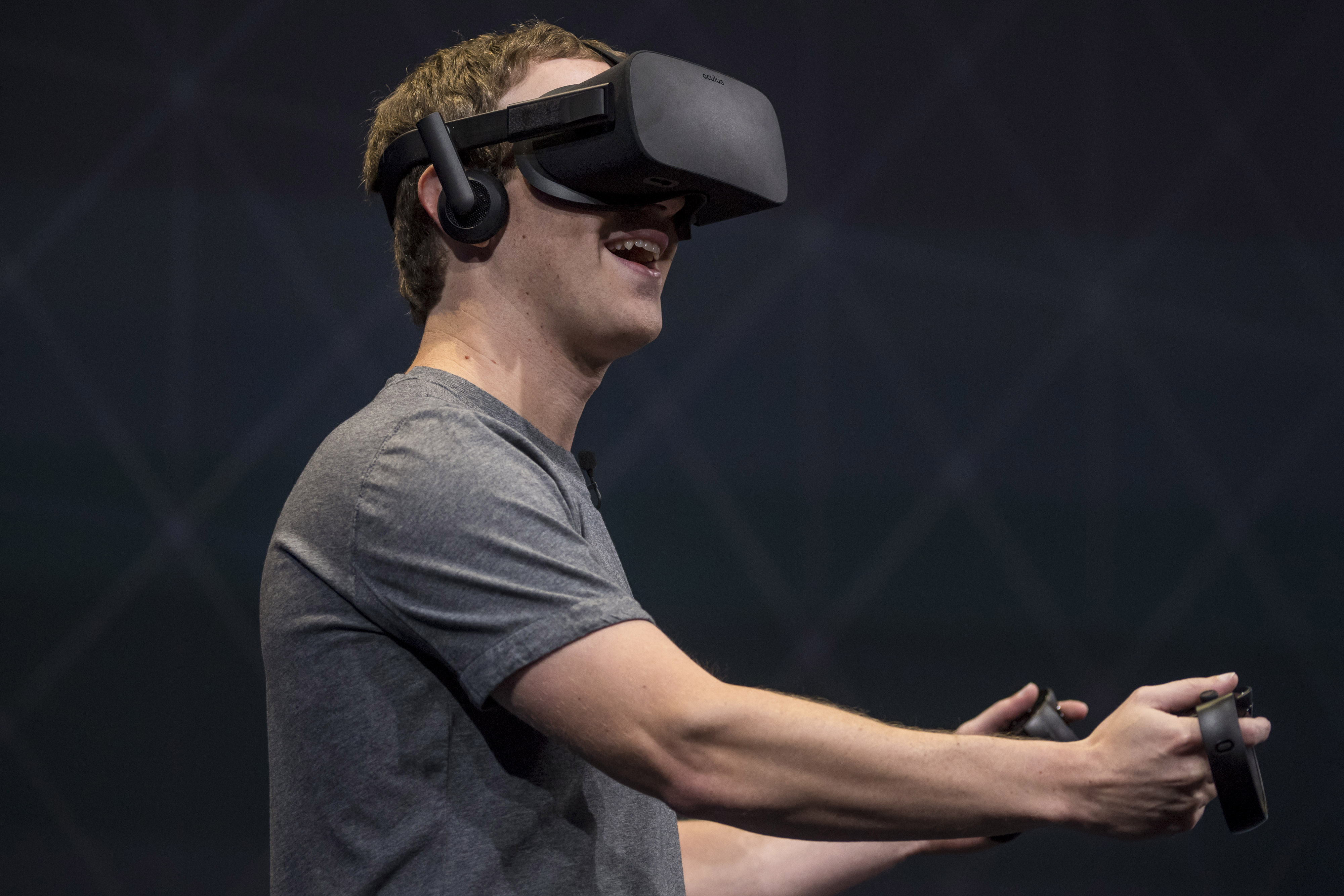 Mark Zuckerberg, chief executive officer and founder of Facebook Inc., demonstrates an Oculus Rift virtual reality (VR) headset and Oculus Touch controllers as the gives a demonstration during the Oculus Connect 3 event in San Jose, California, U.S., on Thursday, Oct. 6, 2016.