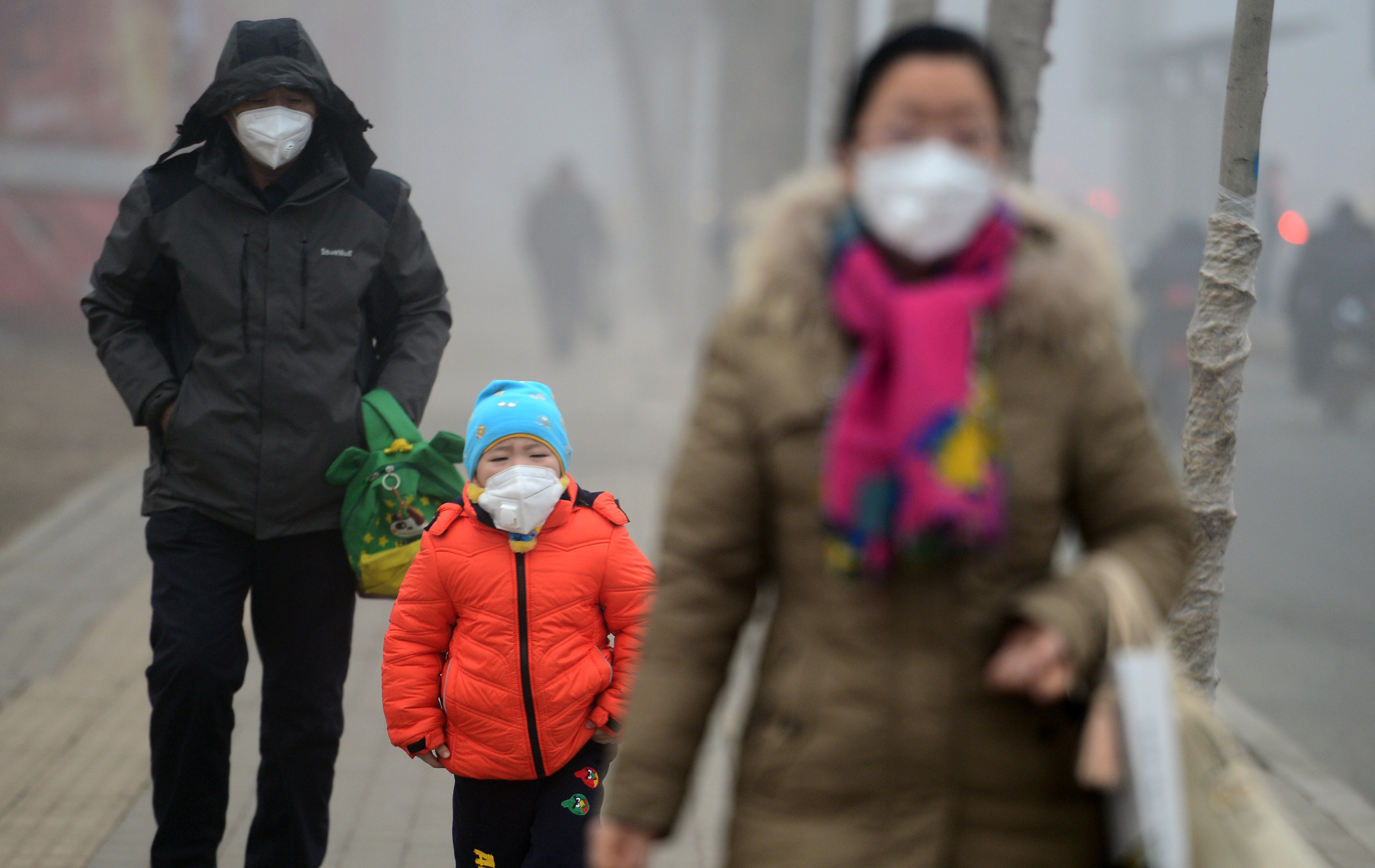 Pedestrians wearing masks walk on a road that is blanketed by heavy smog on Jan. 5, 2017, in Jinan, Shandong province, China