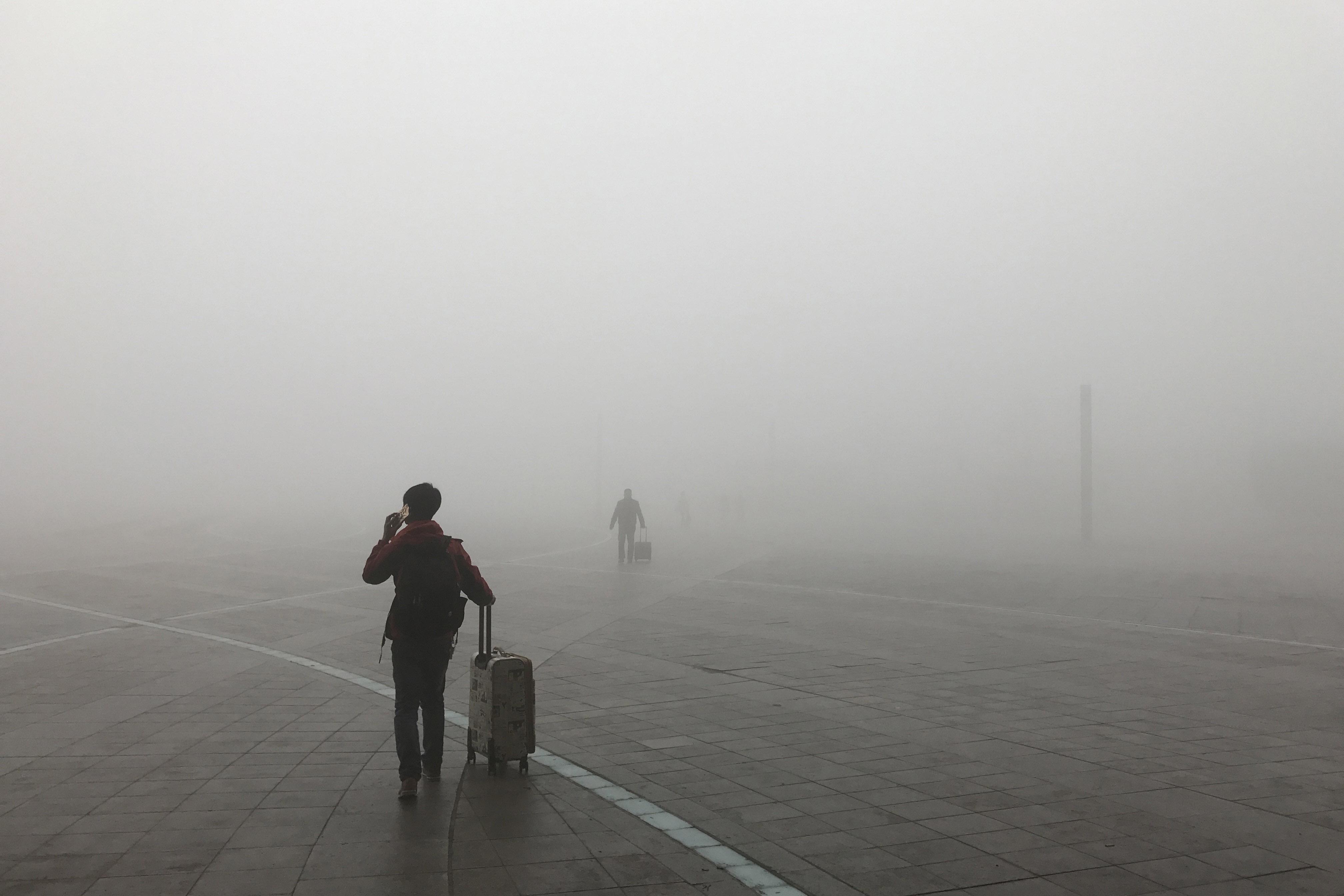 Passengers walk in the smog at Zhengzhou East Railway Station on Jan. 9, 2017, in Zhengzhou, Henan province, China