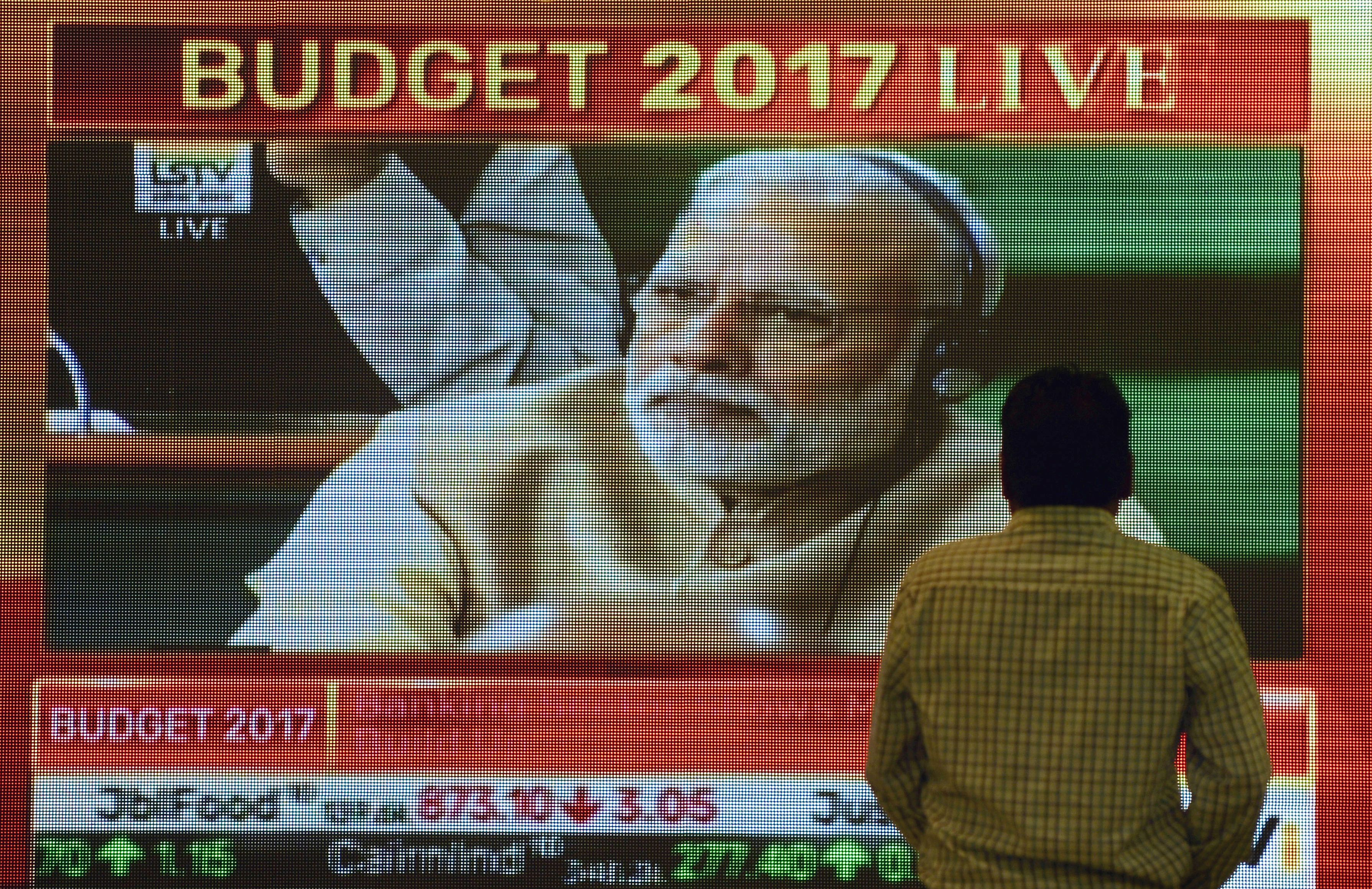 A bystander at the Bombay Stock Exchange walks past a screen showing Indian Prime Minister Narendra Modi listening to Finance Minister Arun Jaitley's delivery of the budget speech at Parliament on Feb. 1, 2017