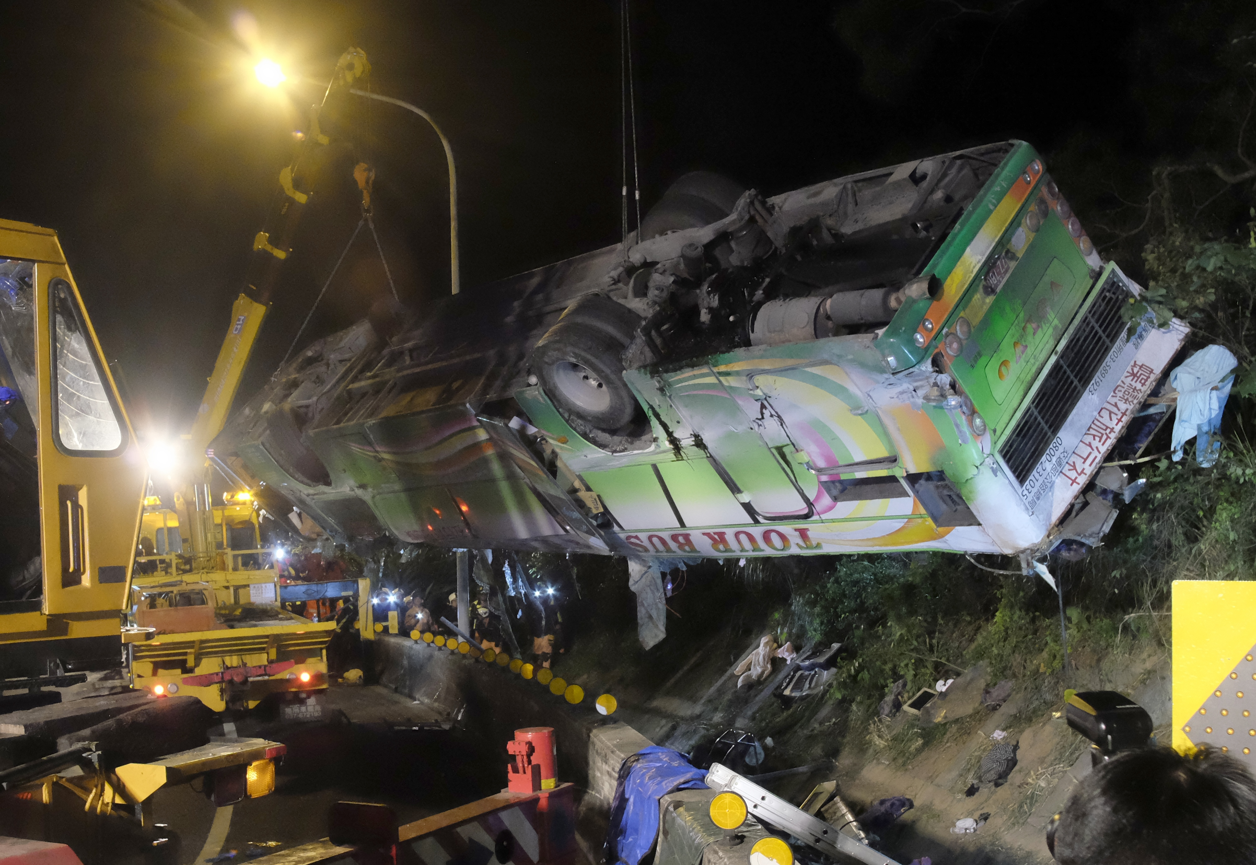 Wreckage of the crashed bus being lifted by cranes, overnight in Taipei on Feb. 14, 2017.