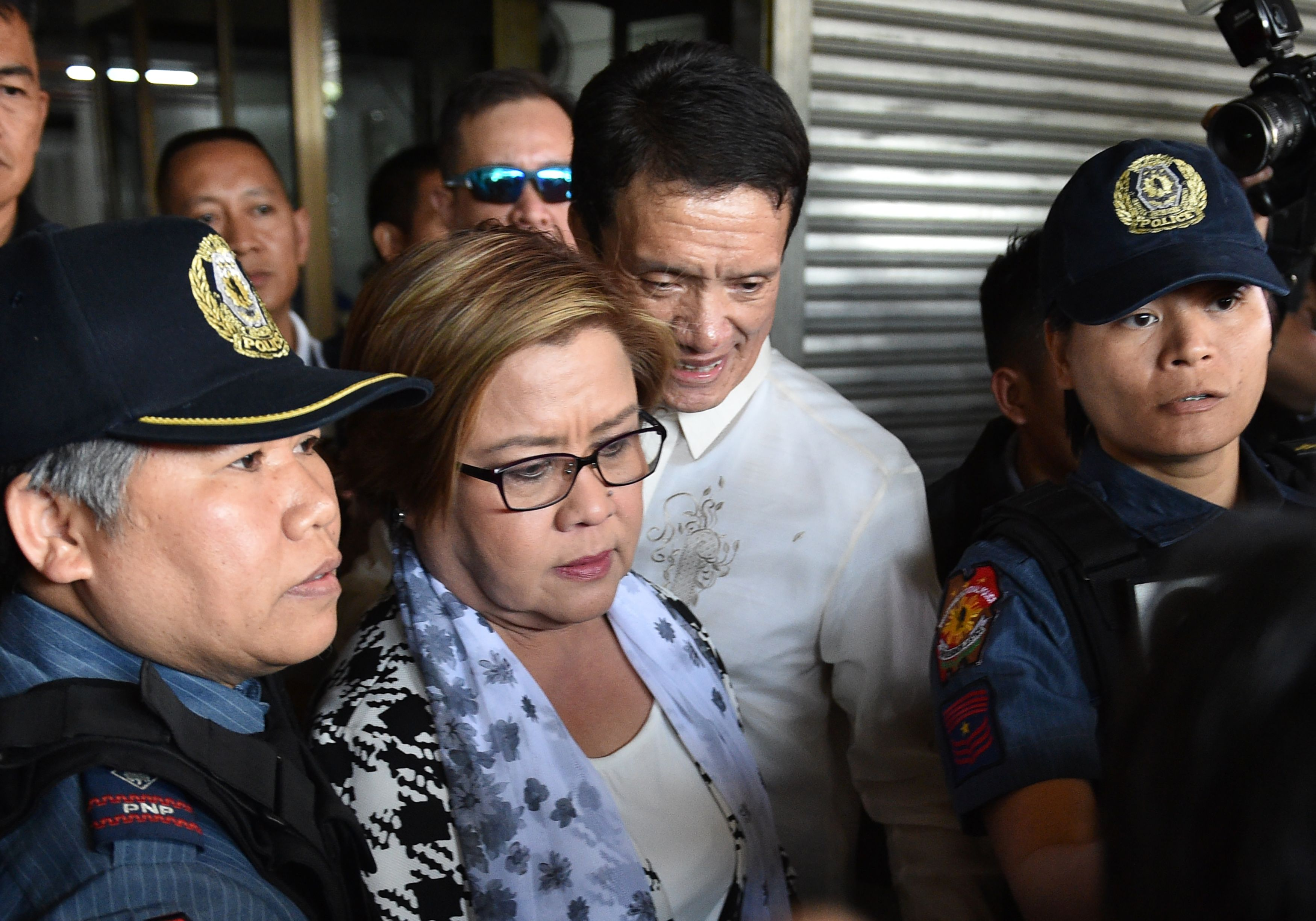Philippine Senator Leila de Lima, center, a top critic of President Rodrigo Duterte, is escorted by police officers and her lawyer after her arrest at the Senate in Manila on Feb. 24, 2017