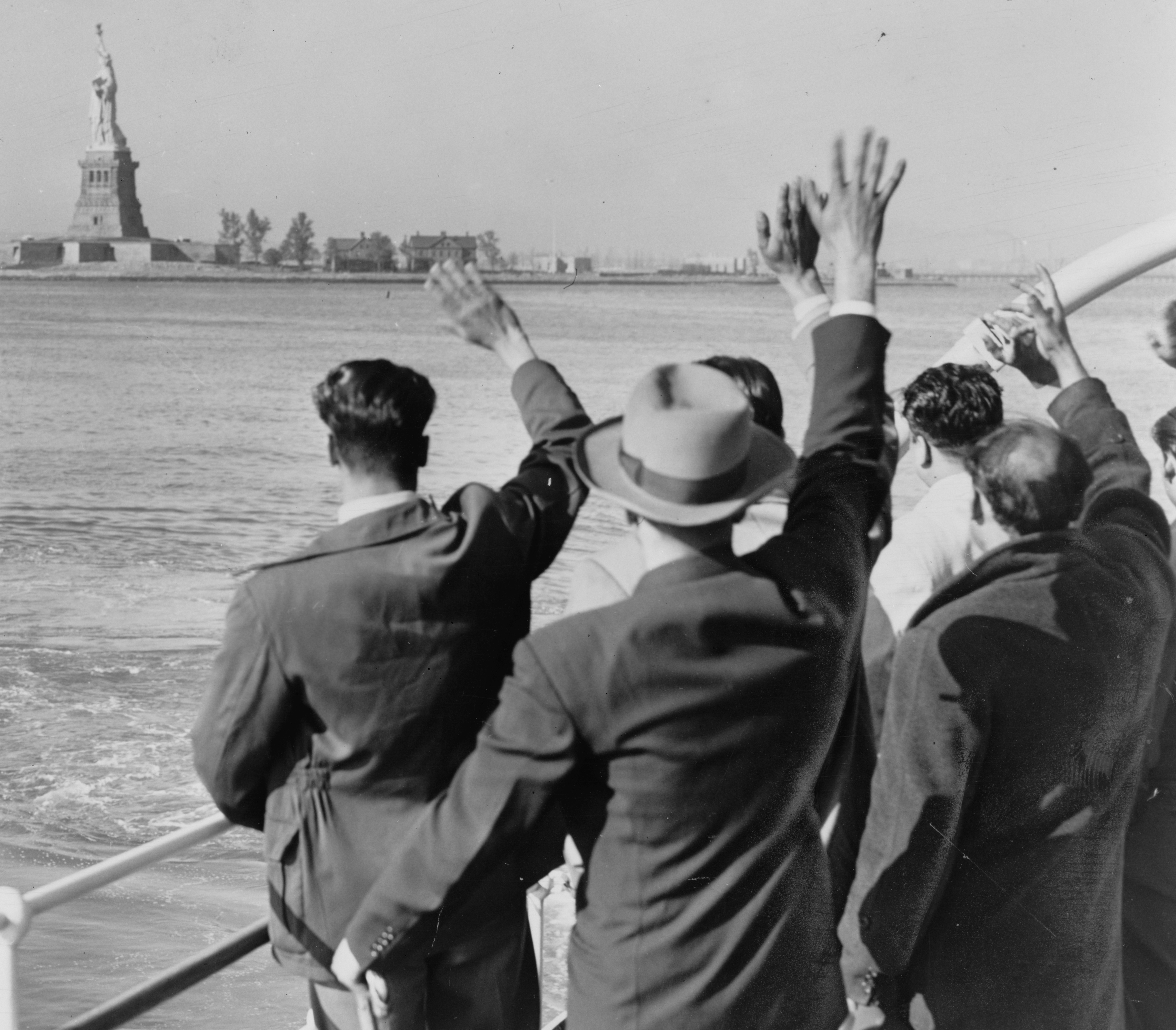 Circa 1952, a group of 171  illegal aliens  wave goodbye to the Statue of Liberty from the Coast Guard cutter that took them from Ellis Island to the Home Lines ship 'Argentina' in Hoboken for deportation.