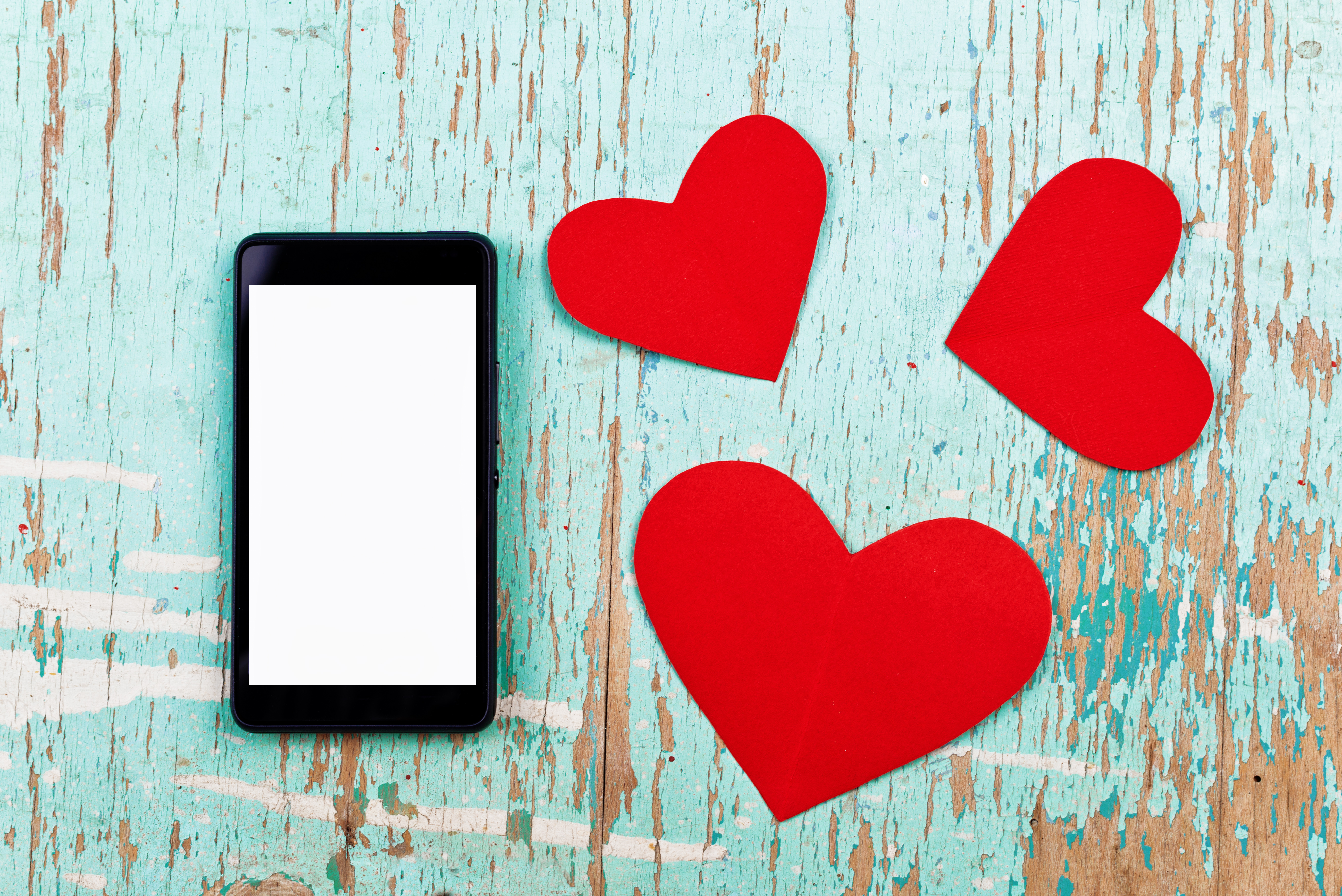 Valentine's Day copy space on smart phone with blank screen and red paper hearts on old grunge wood texture.