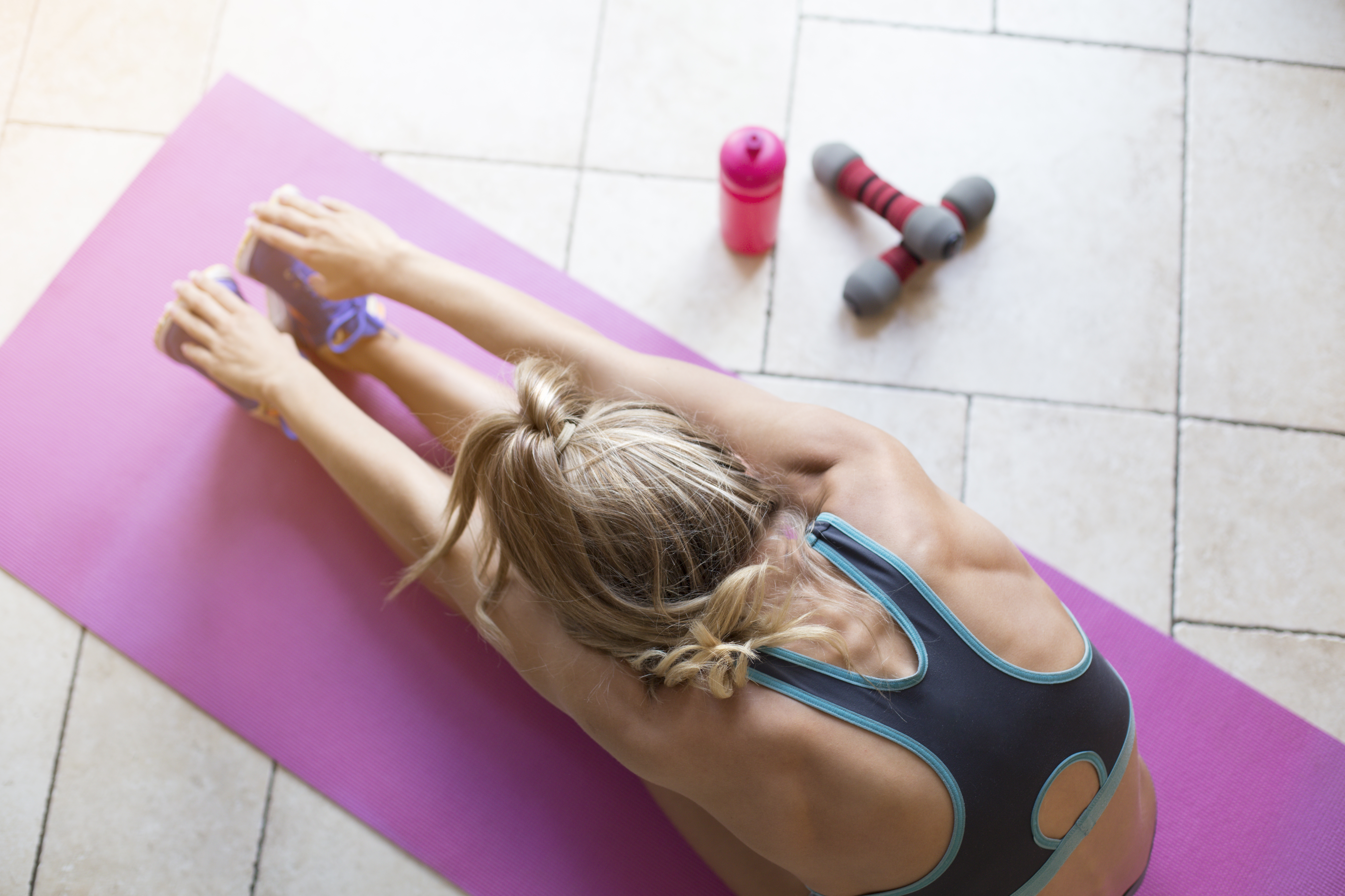 Young woman stretching after a workout at home