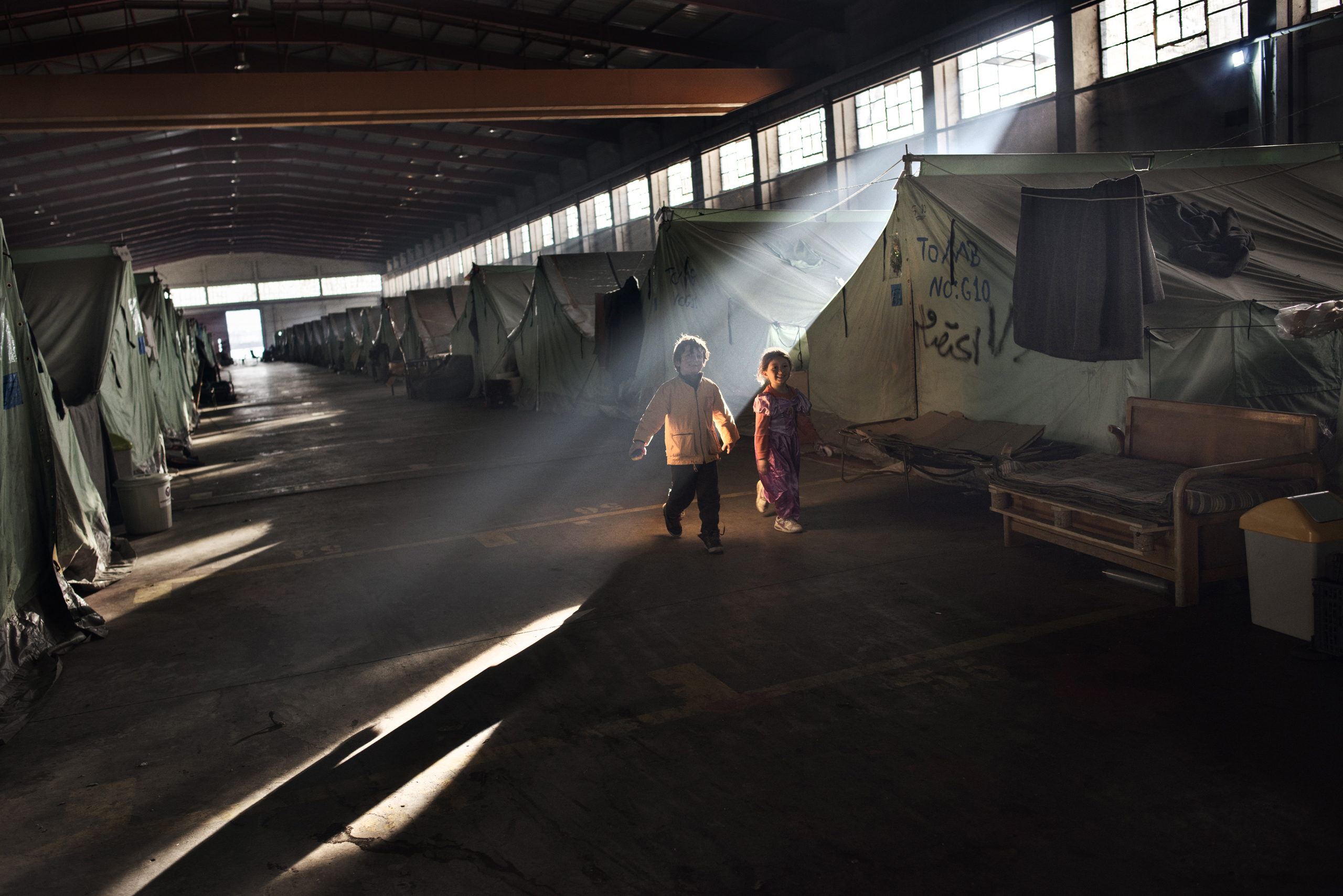 Syrian refugee children run through smoke emitted from fires lit by refugees trying to stay warm at the Oreokastro camp, where many refugees have already been moved to hotels, January 13, 2017.