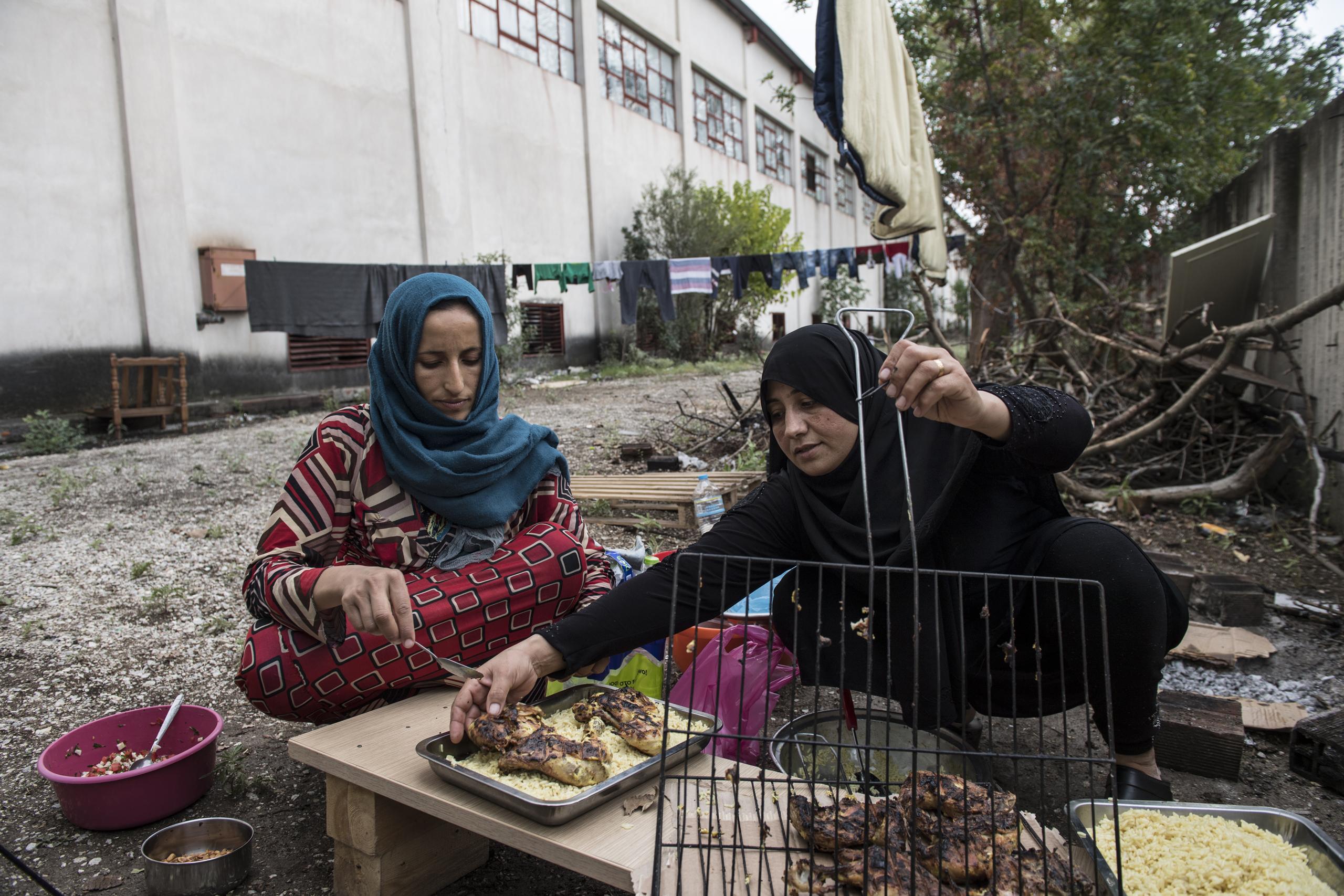 Illham Alarabi cooks outside the Oreokastro camp, Sept. 9, 2016,