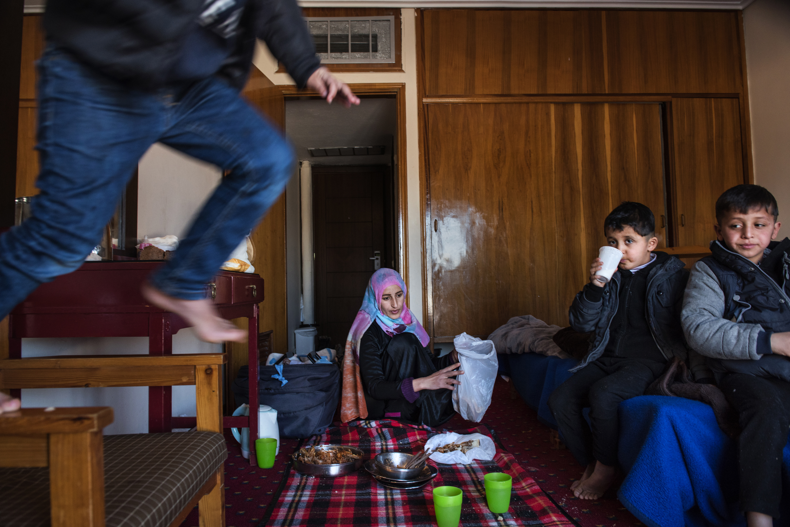 23-year-old Illham Alarabi cleans sits on the floor after eating lunch as her sons play in their hotel room in Kastoria, in Greece near the Albanian border, Jan 14, 2017.   Ilham's fifth son, Faraj, was born on October 2, 2016.  Her days are a whirlwind of cooking, cleaning and childcare with only the barest assistance.