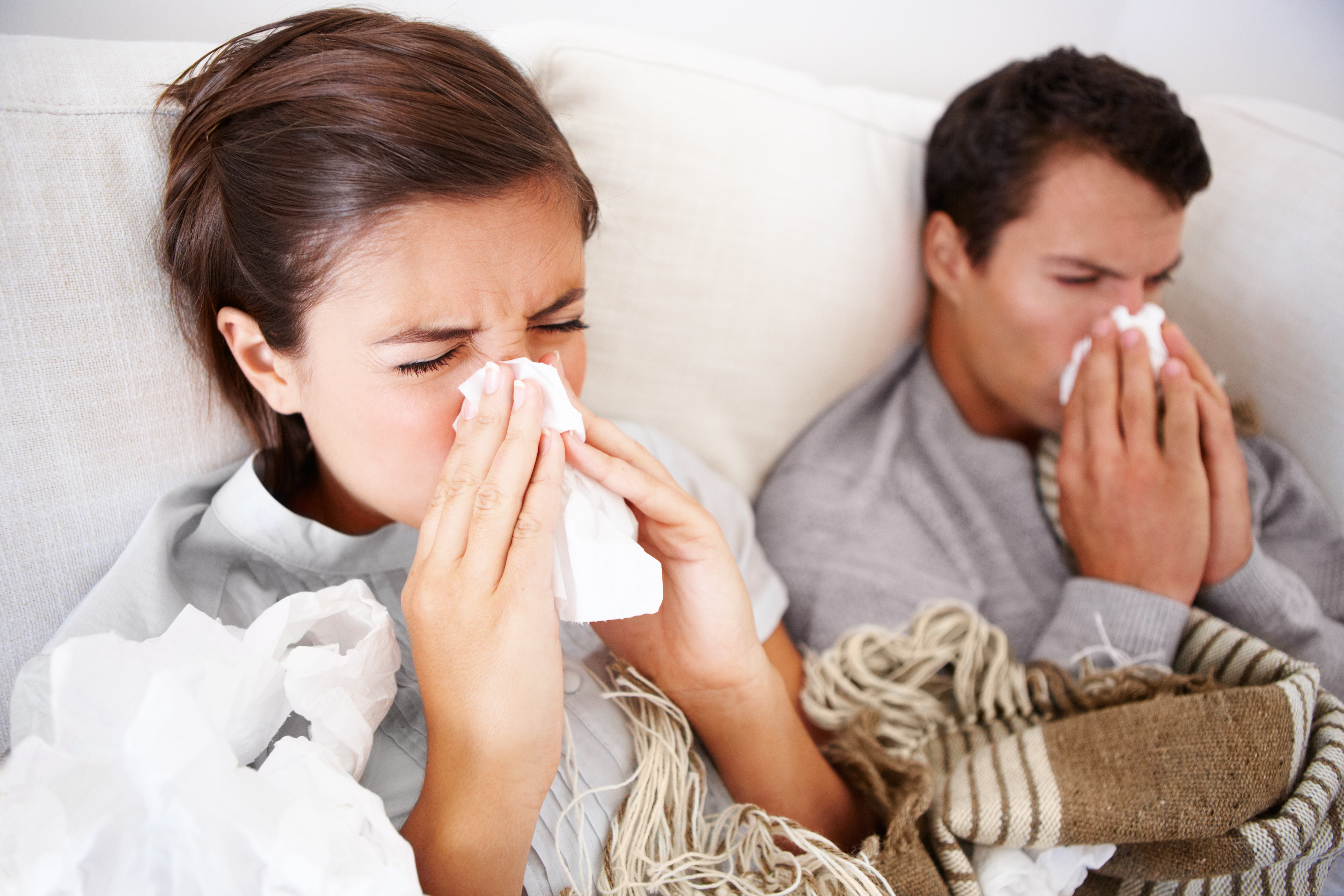 Young couple fighting the flu as they both lay in bed