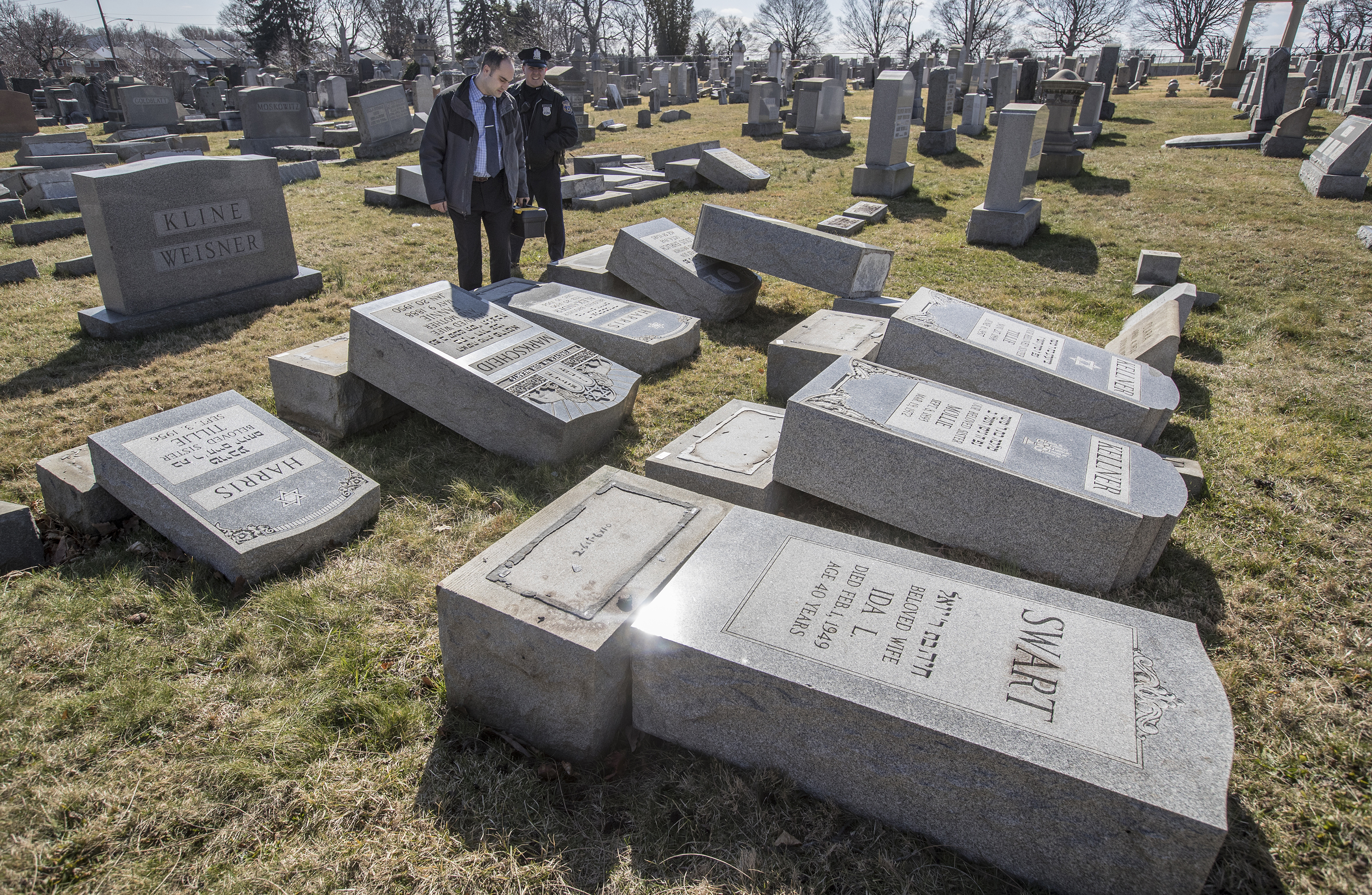 Northeast Philadelphia Police Det. Timothy McIntyre and another Philadelphia police officer look over tombstones that were vandalized in the Jewish Mount Carmel Cemetary Sunday, Feb. 26, 2017 in Philadelphia.