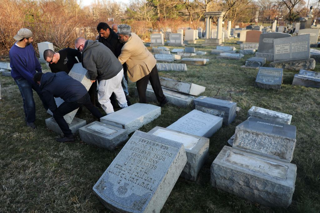 Volunteers help lift a fallen tombstone at the Jewish Mount Carmel Cemetery on Feb. 26, 2017, in Philadelphia.