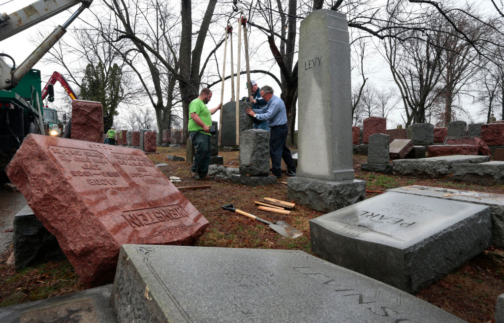 Spencer Pensoneau, left, Ron Klump and Philip Weiss of Rosenbloom Monument Company re-set stones at Chesed Shel Emeth Cemetery in University City on Feb. 21, 2017 where almost 200 gravestones were vandalized over the weekend in St. Louis.