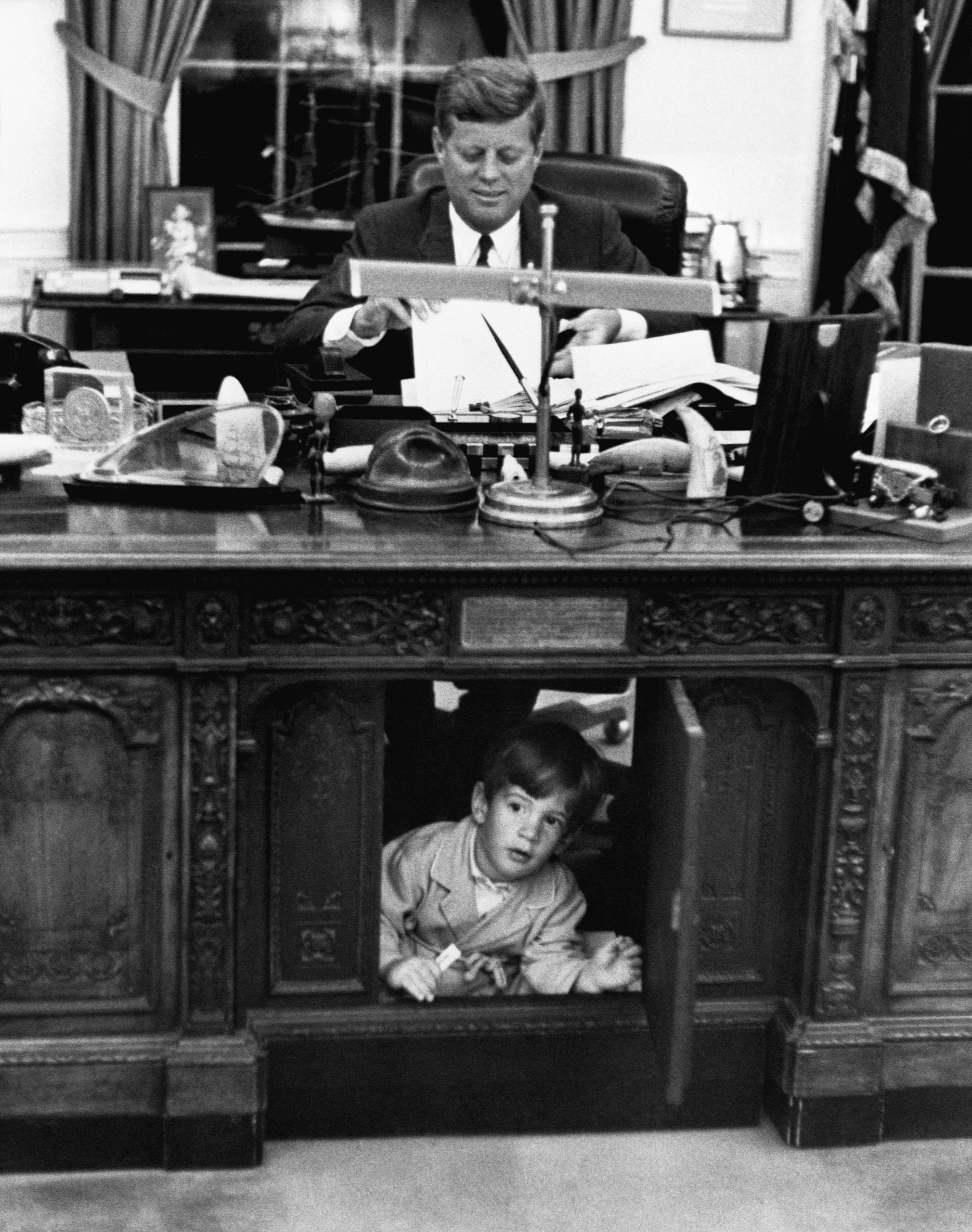 Pres. John F. Kennedy playing w. his son John F. Kennedy Jr. at his desk in the Oval Office. 1963.