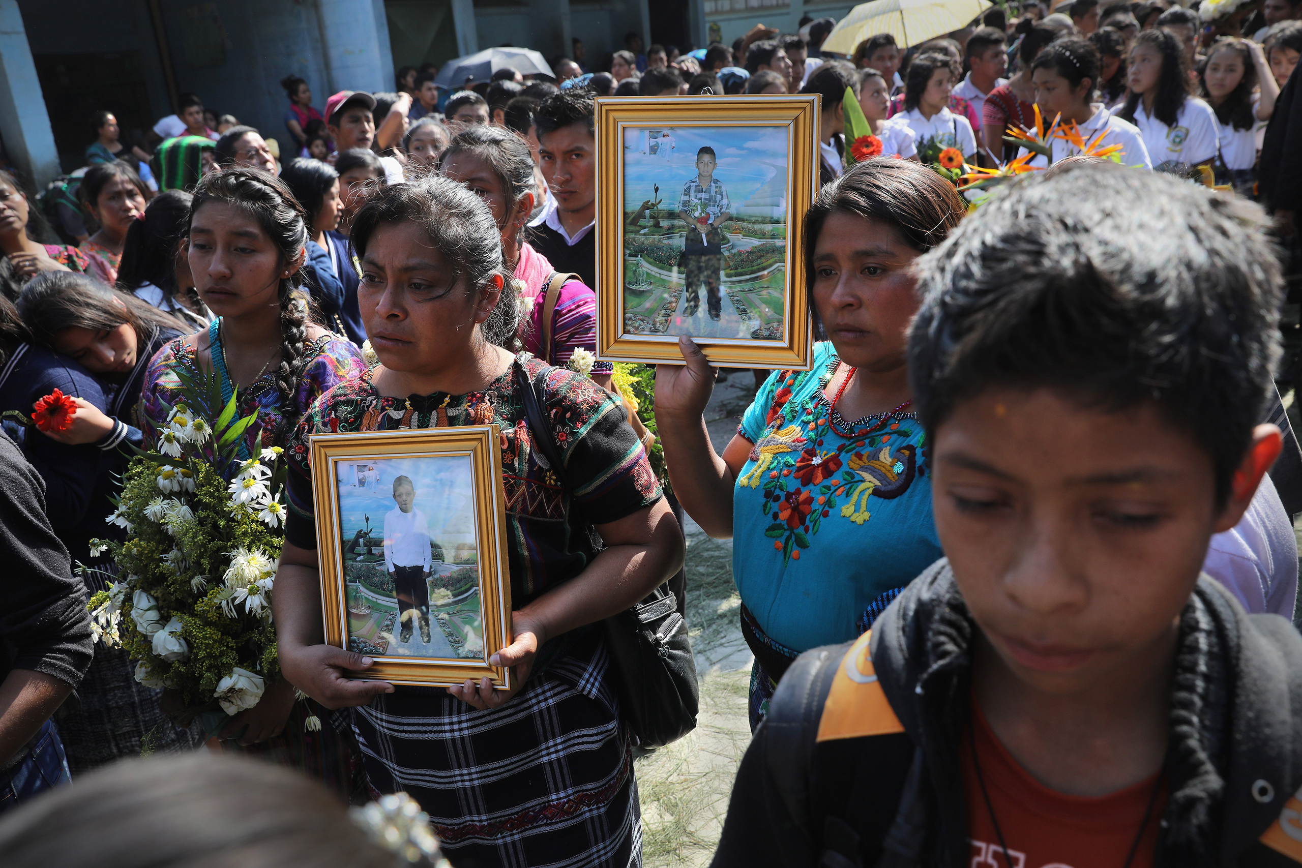 Mothers carry portraits of their sons who were kidnapped and killed in San Juan Sacatepéquez on Feb. 14, 2017.