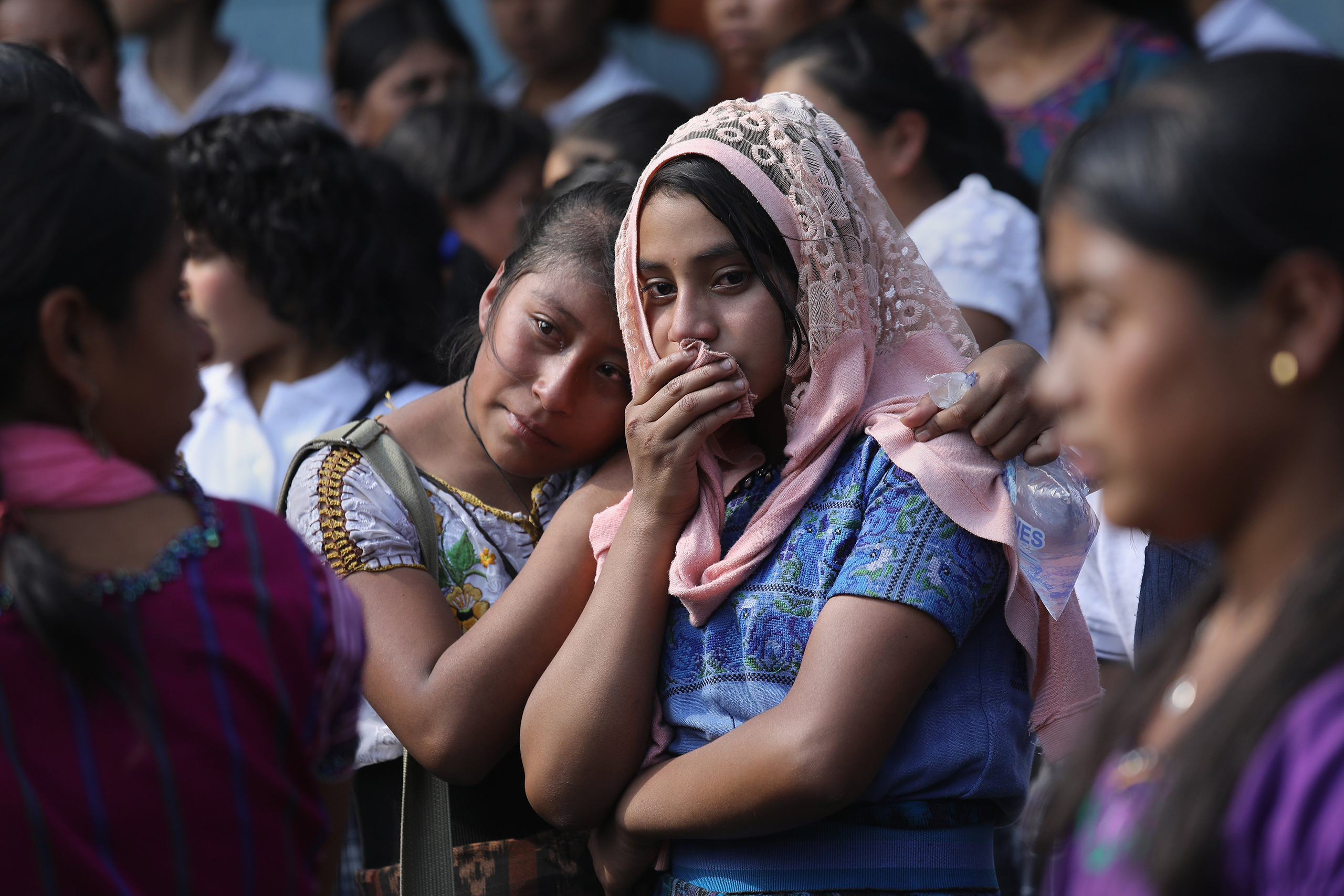 Two girls mourn at a memorial service held at the elementary school attended by two boys who were kidnapped and killed in San Juan Sacatepéquez on Feb. 14, 2017.