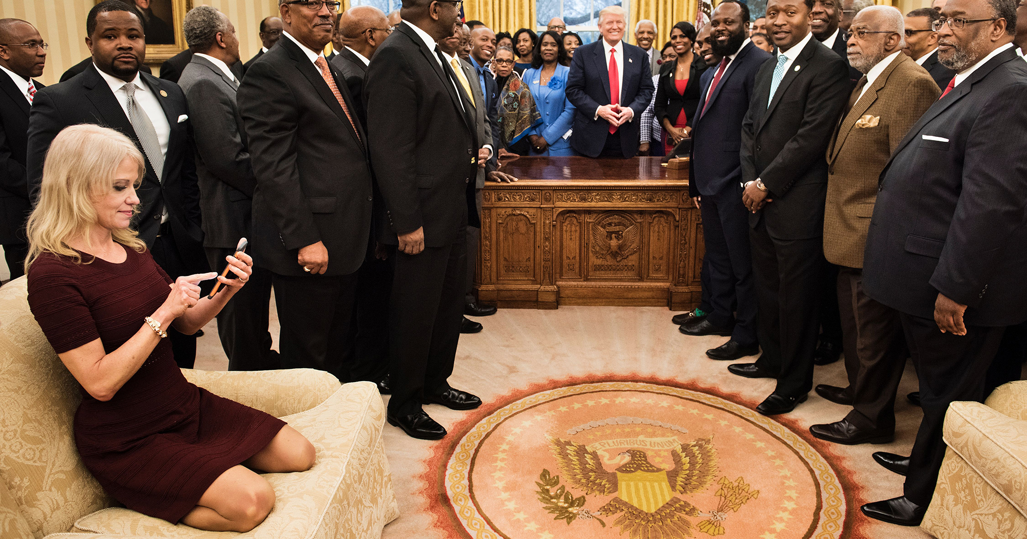 Counselor to the President Kellyanne Conway checks her phone after taking a photo as President Donald Trump and leaders of historically black universities and colleges pose for a group photo in the Oval Office, on Feb. 27, 2017 in Washington, D.C.