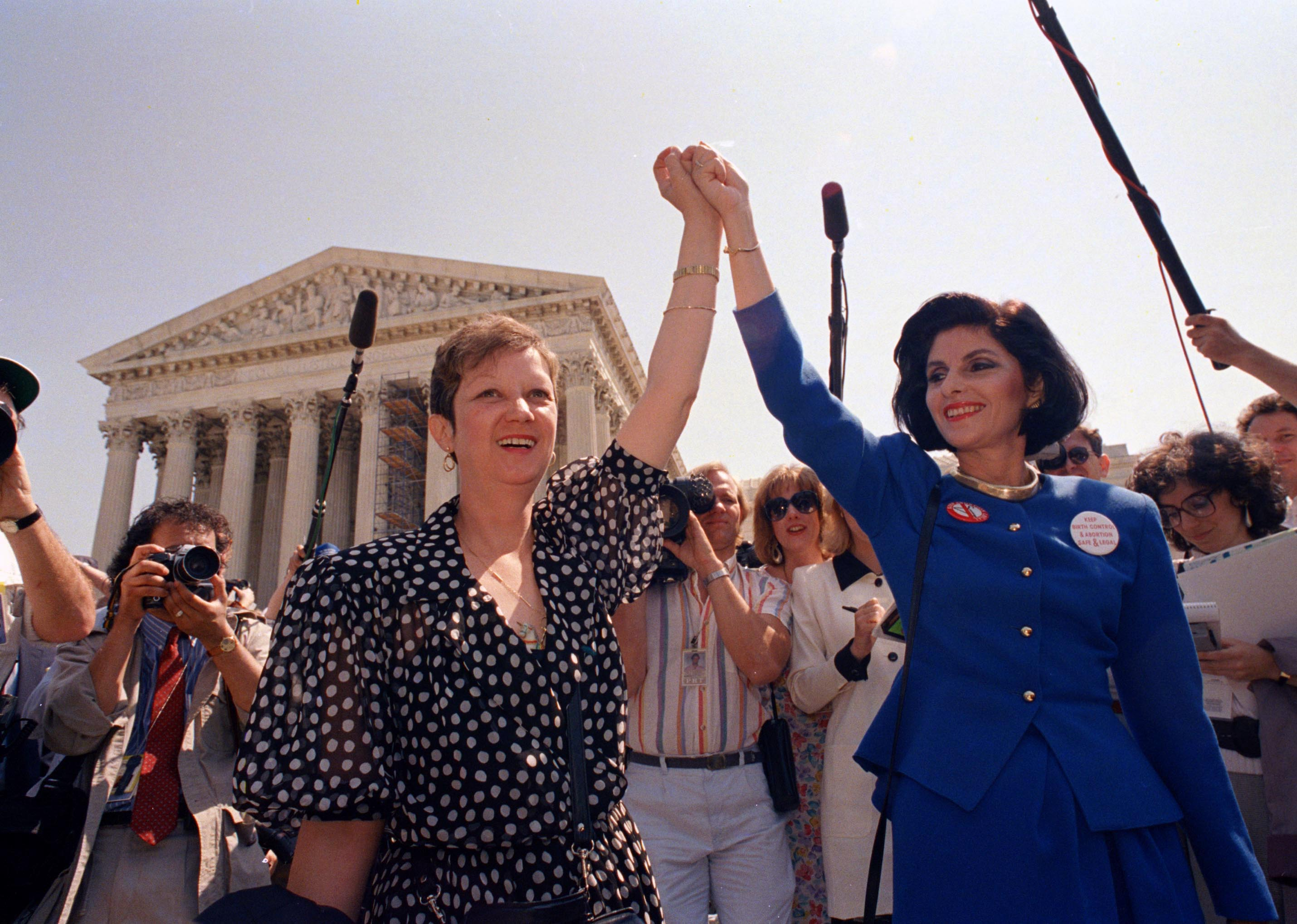 Norma McCorvey, Jane Roe in the 1973 court case, left, and her attorney Gloria Allred hold hands as they leave the Supreme Court building in Washington, DC., on April 26, 1989.