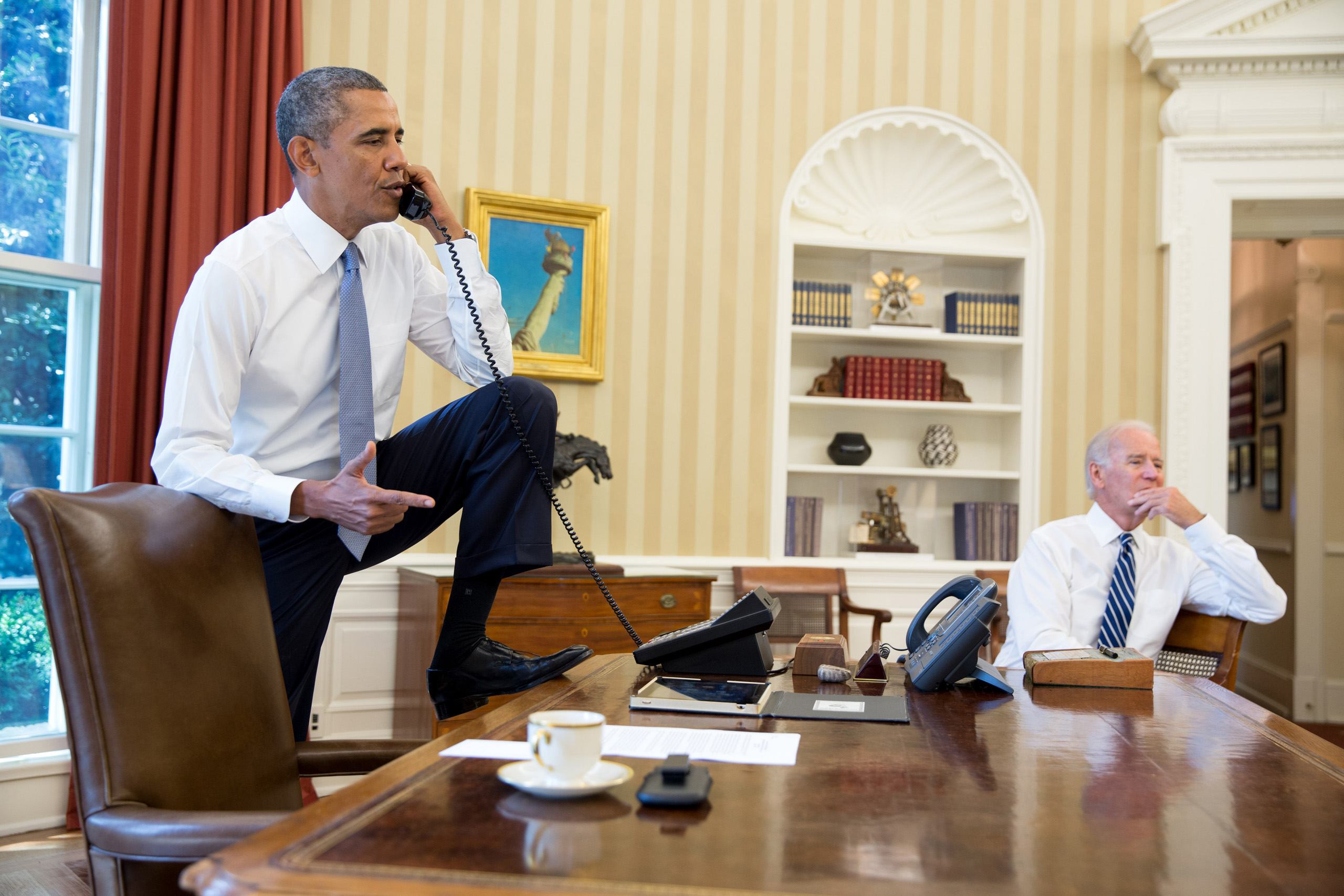 U.S. President Barack Obama (L) talks on the phone with Speaker of the House Boehner as Vice President Joe Biden listens in the Oval Office of the White House August 31, 2013 in Washington, DC.
