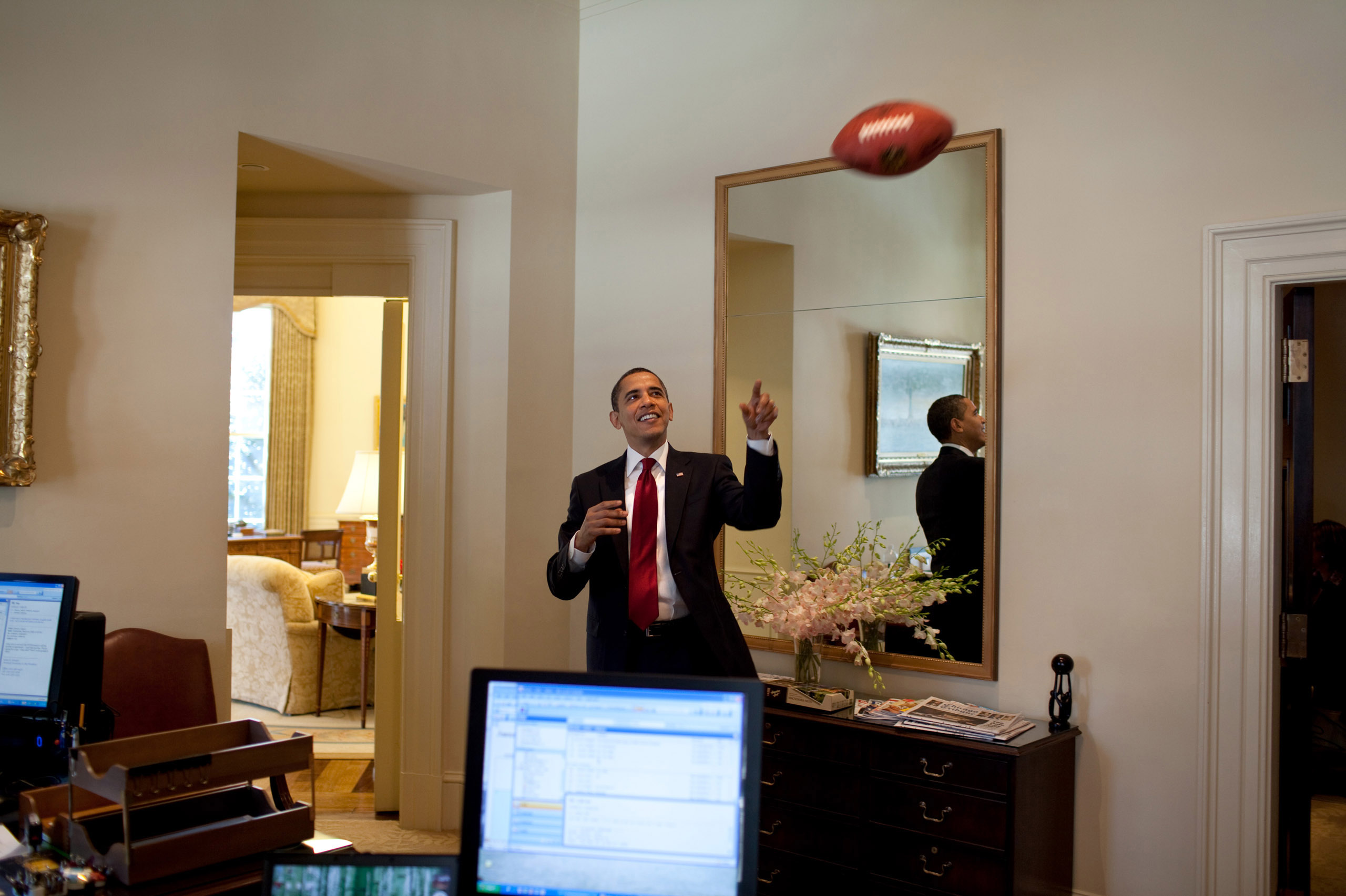 U.S. President Barack Obama plays with a football in the Outer Oval Office of the White House on March 4, 2009 in Washington, DC.