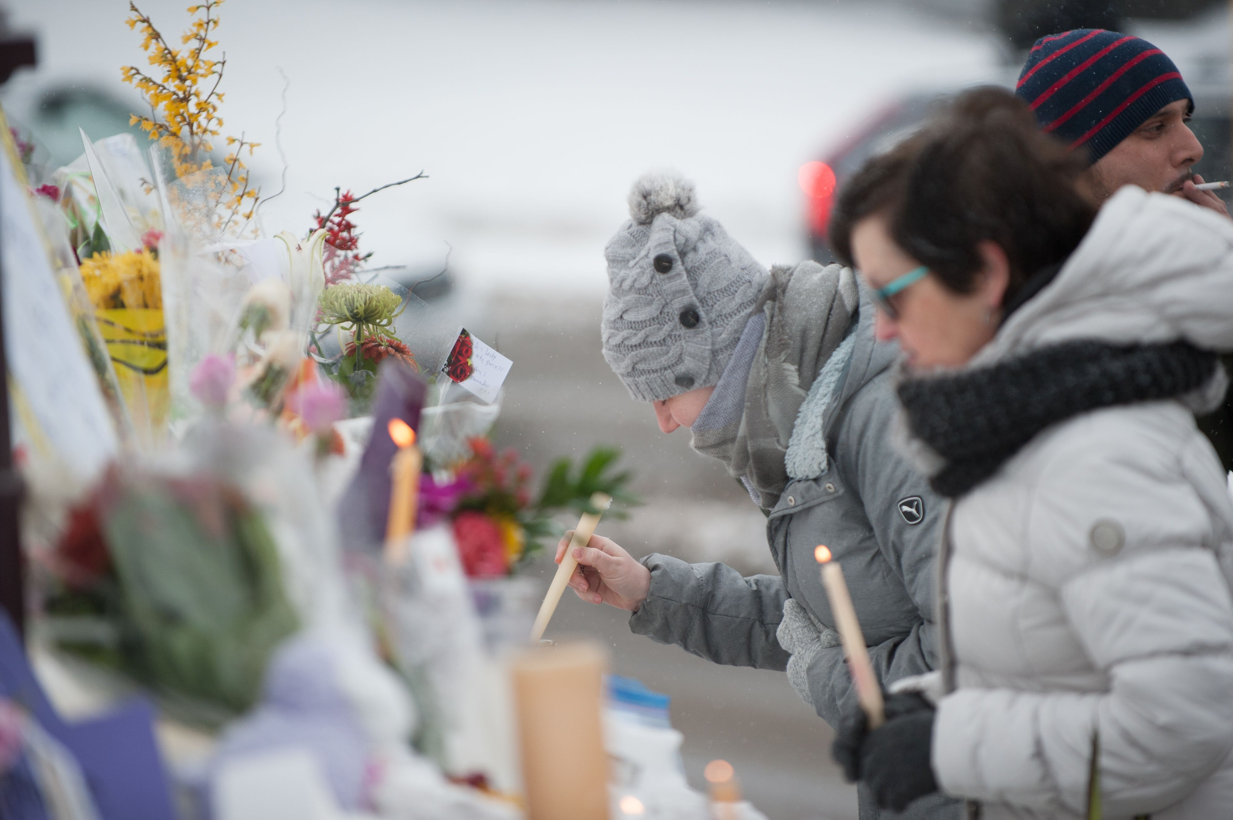 People visit a makeshift memorial near a mosque that was the location of a shooting spree in Quebec City, on Feb. 1, 2017.