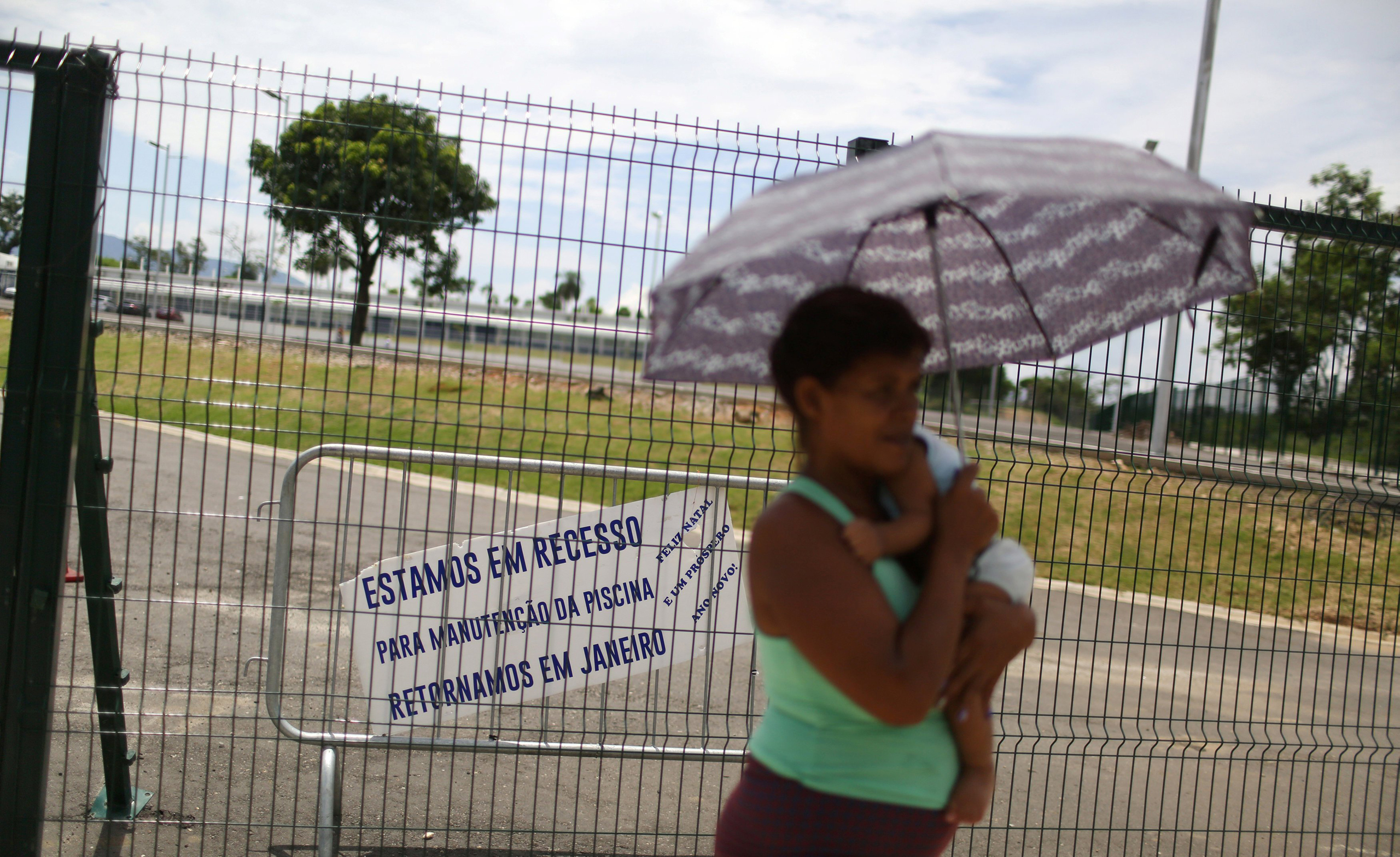A woman carries a baby in front of the Deodoro Sports Complex, which was used for the Rio 2016 Olympic Games, in Rio de Janeiro, Brazil, on Feb. 7, 2017. The sign reads:   We are in recess for maintenance of the pool, we will return in January. Merry Christmas and Happy new year .