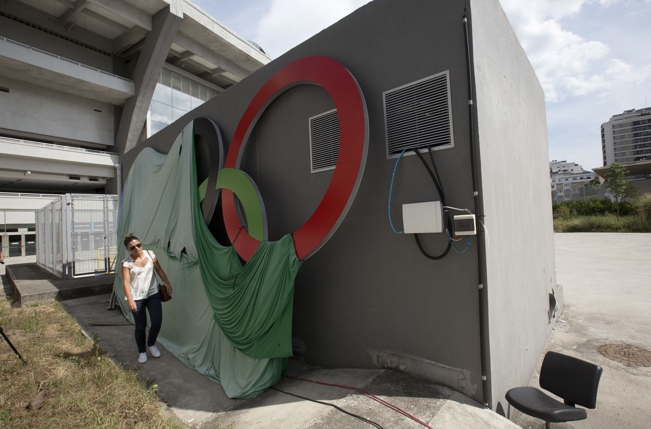 A woman walks past Olympic rings covered with a canvas at Maracana stadium in Rio de Janeiro, Brazil on Feb. 2, 2017.