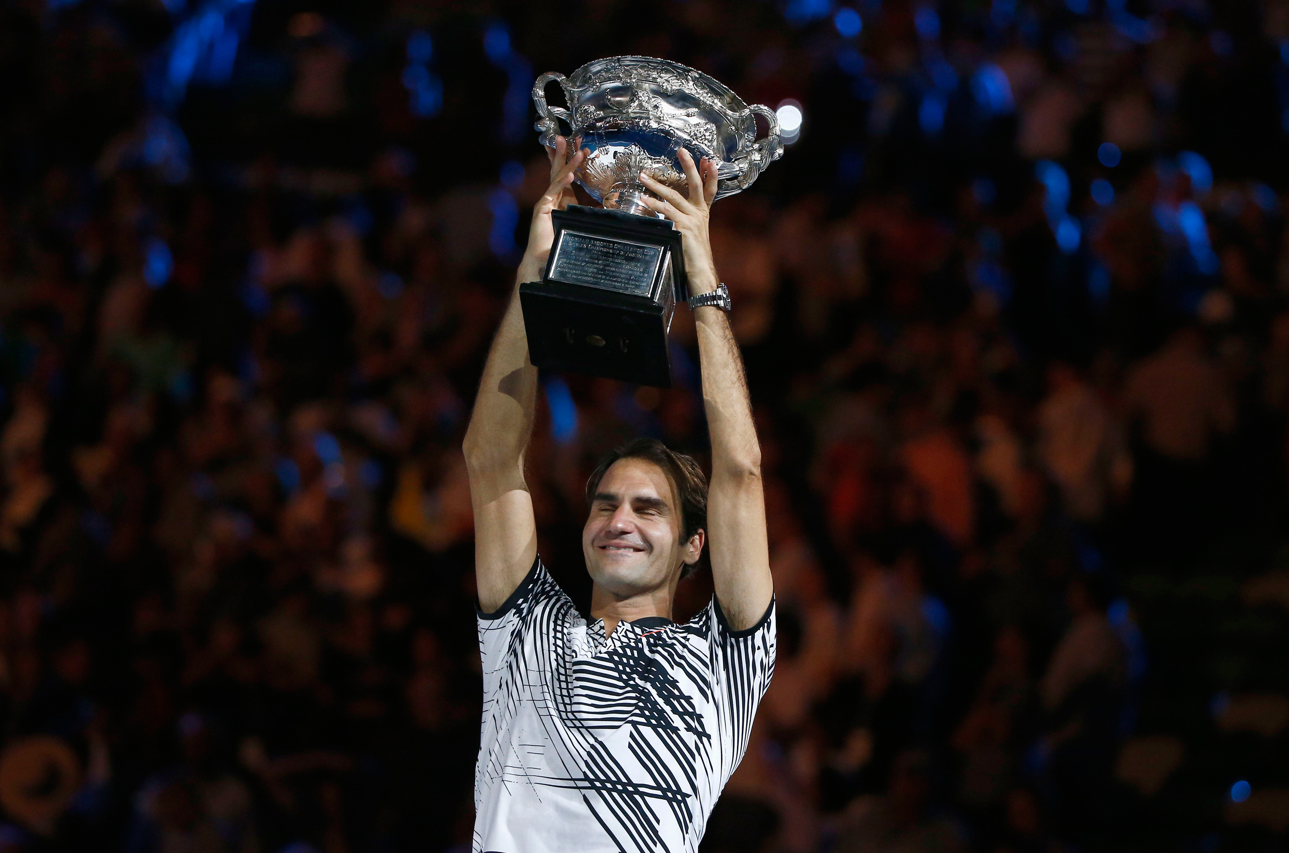 Switzerland's Roger Federer holds up the trophy after winning the Australian Open Men's singles final match against Spain's Rafael Nadal in Melbourne on Jan. 29, 2017.