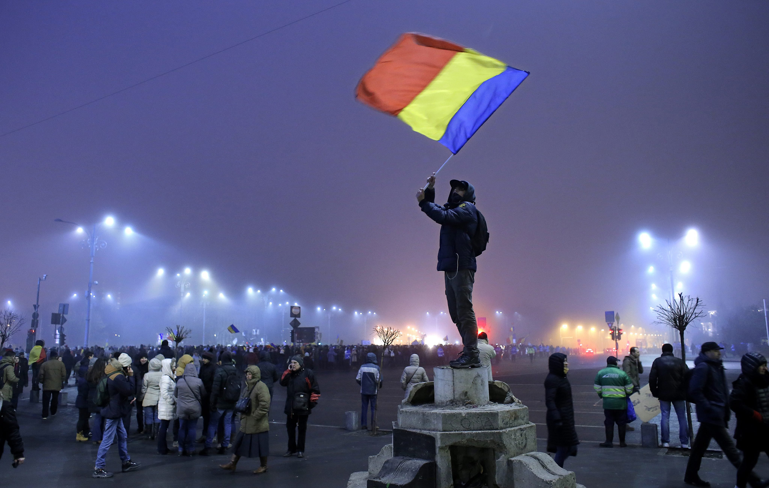 A young man who climbed atop a pedestal waves a Romanian national flag during an antigovernment protest in Bucharest on Feb. 6, 2017.